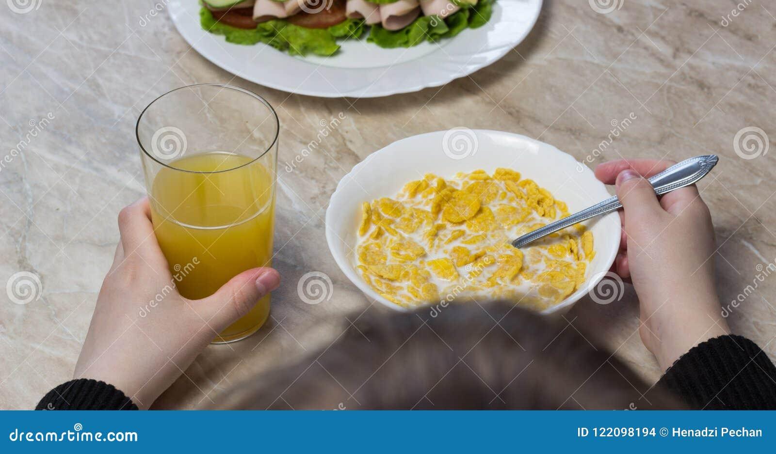 女孩吃玉米片用在学校女小学生前面的牛奶