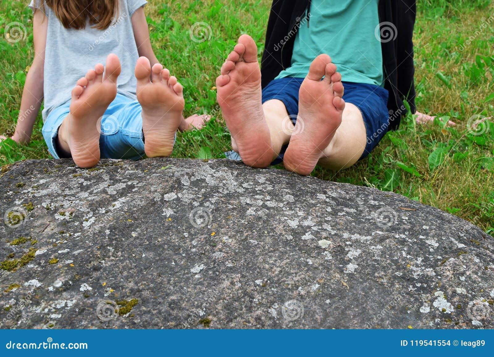 女孩和男孩的赤脚岩石的
