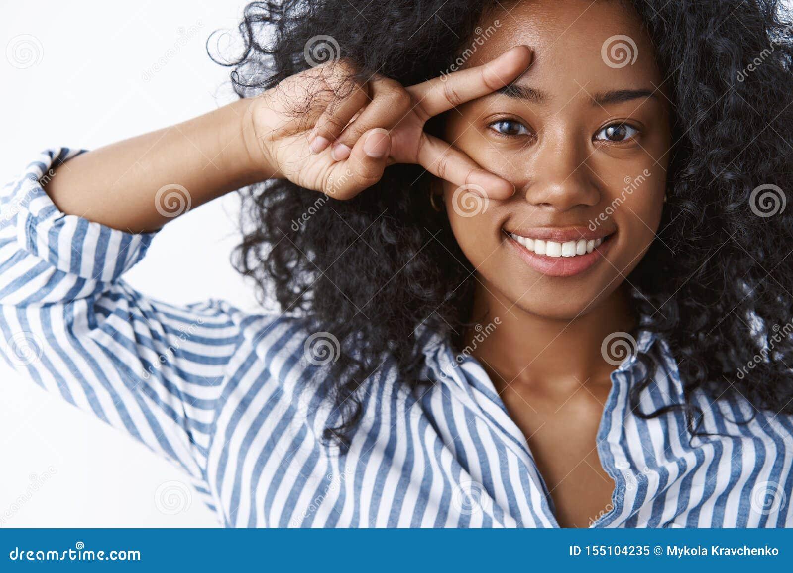 女孩喜欢显示和平标志的芳香树脂 画象感情无忧无虑的愉快的深色皮肤的年轻女人卷曲发型做迪斯科