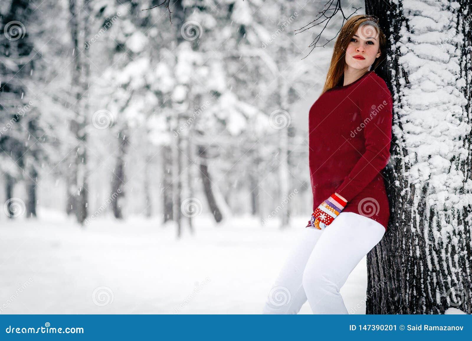 女孩在一件褐红的毛线衣穿戴了,并且白色裤子倾斜了反对树干反对积雪的冬天背景