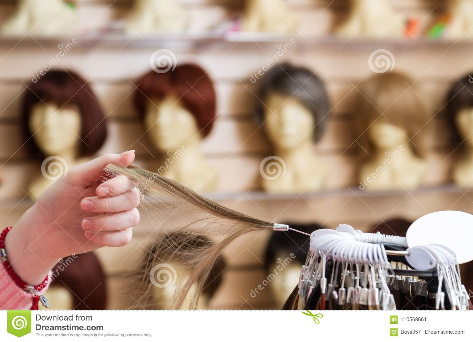 女孩在她的手上选择头发颜色假发一自然白肤金发 头发颜色颜色调色板在假发商店在a的