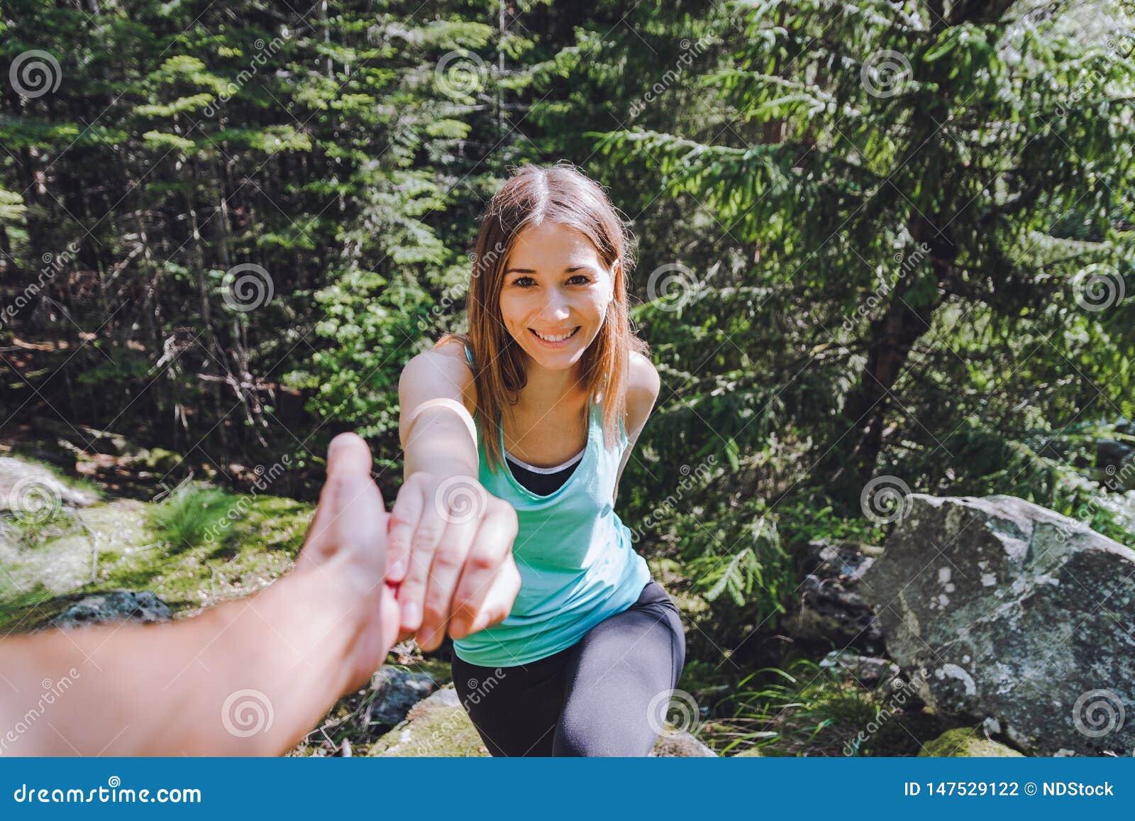 女孩在岩石,伙伴上升拔出协助的手