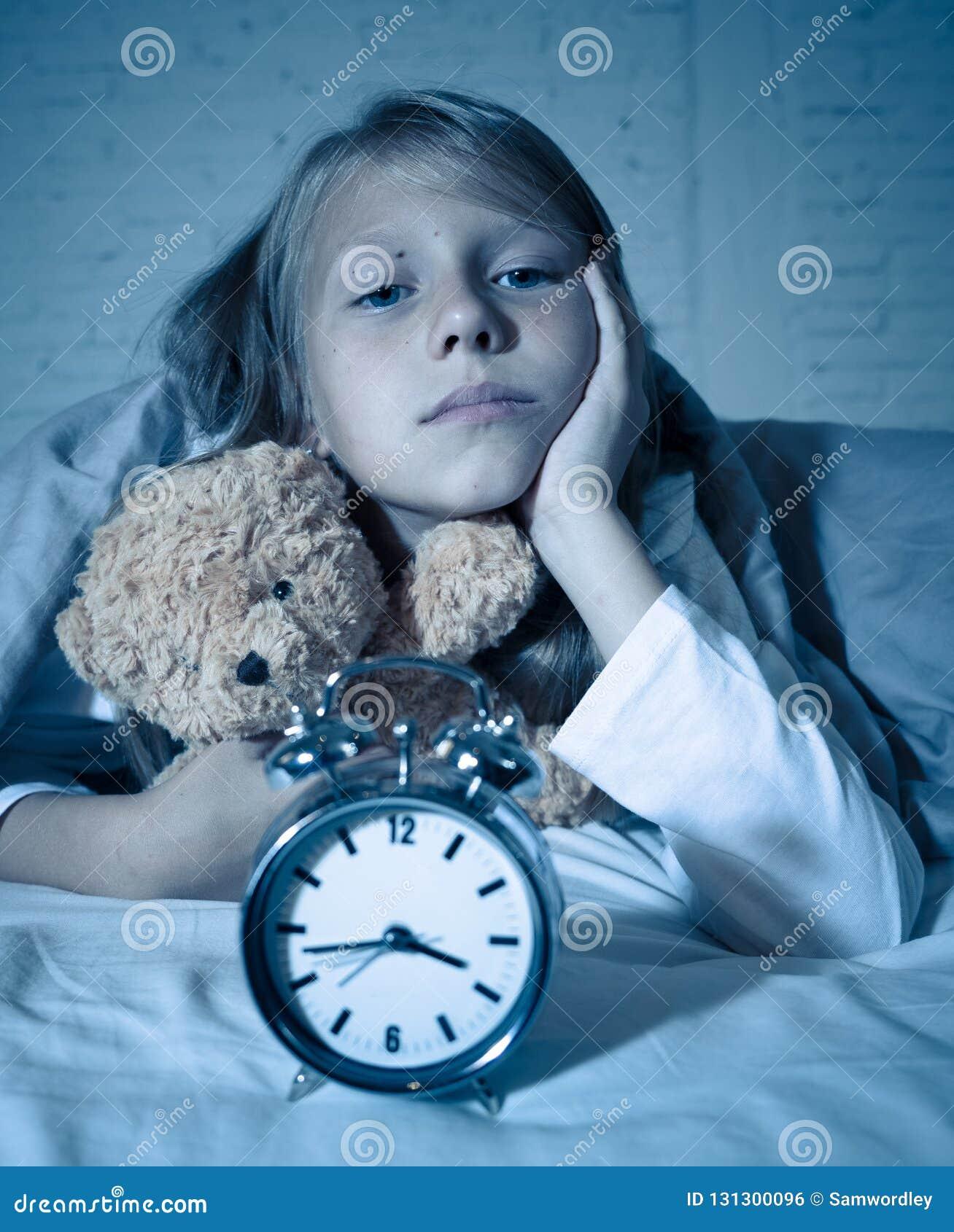 女孩在床上醒在感到的晚上打呵欠和不安定显示时钟她不可能睡觉