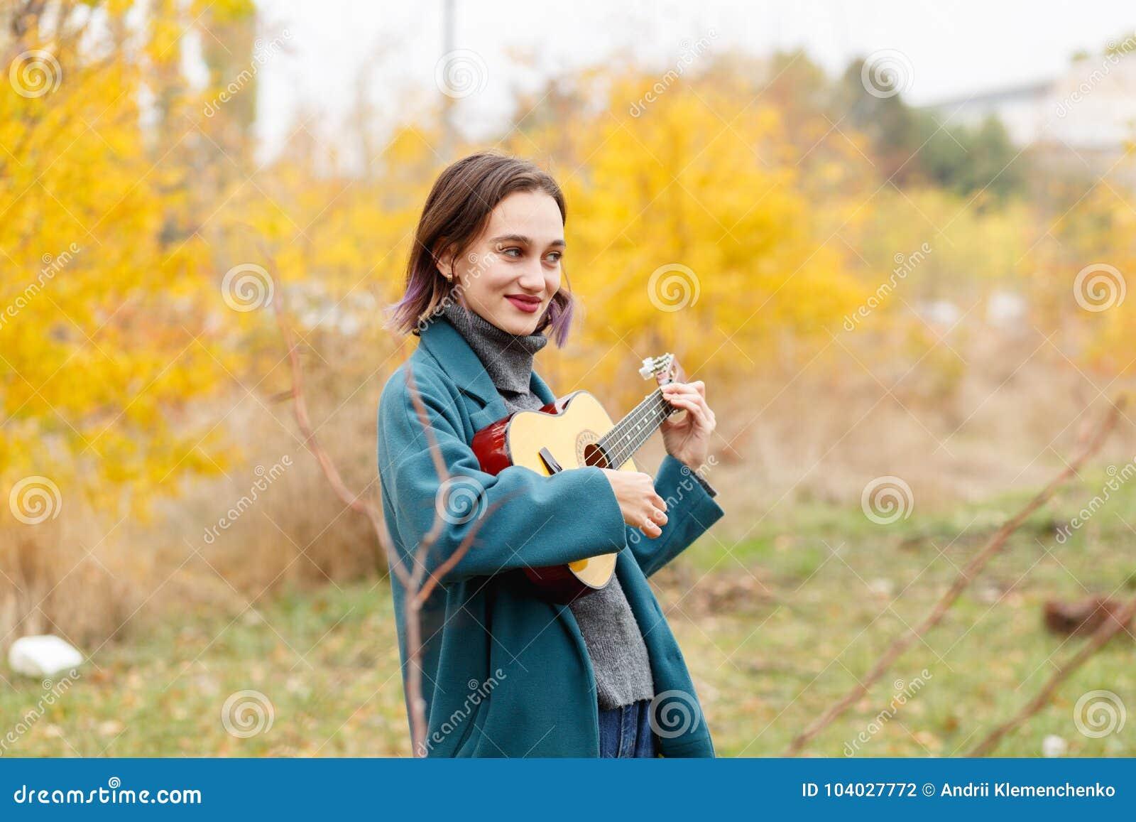 女孩在弹吉他的秋天公园