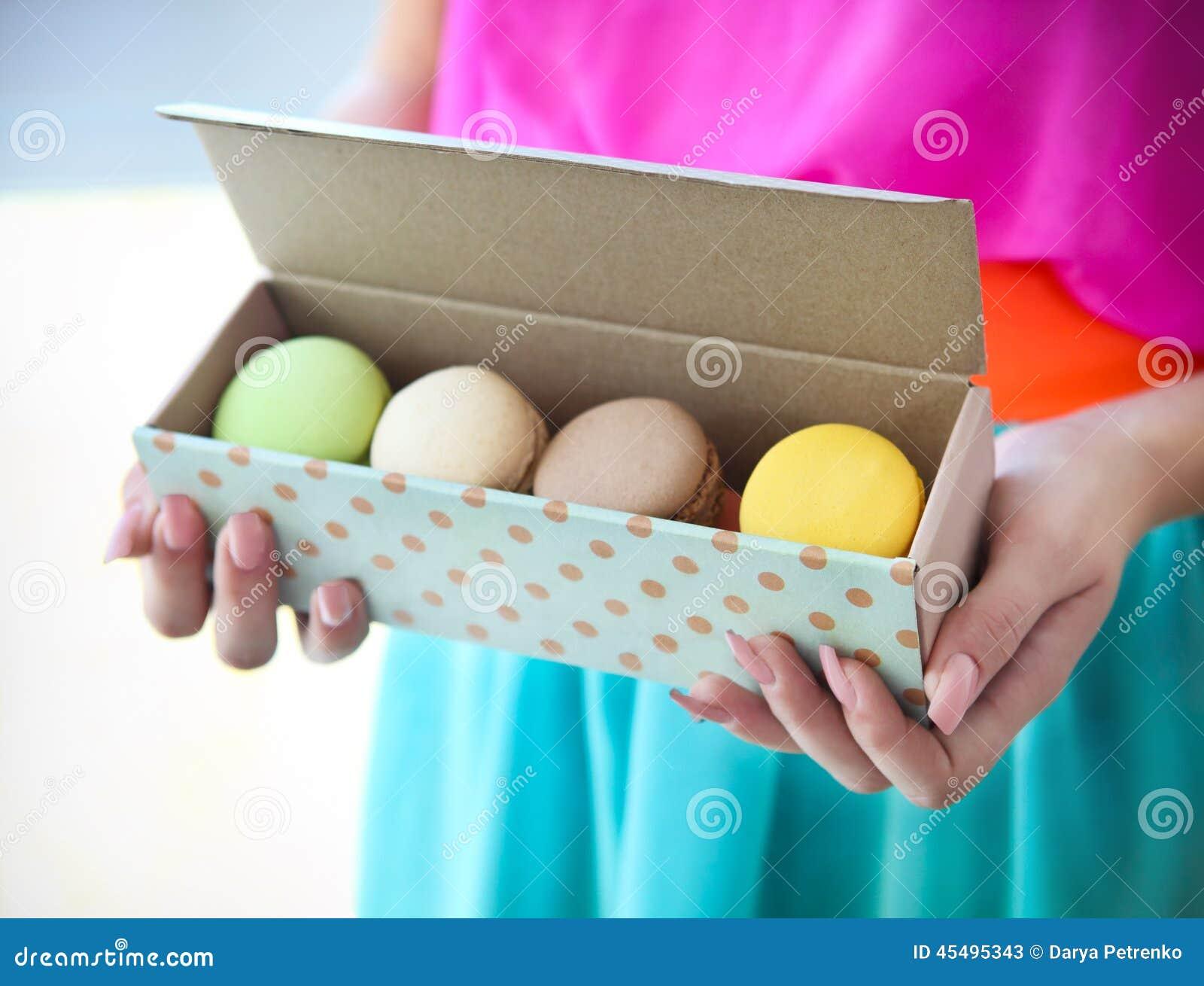 女孩在手上的拿着五颜六色的法国蛋白杏仁饼干
