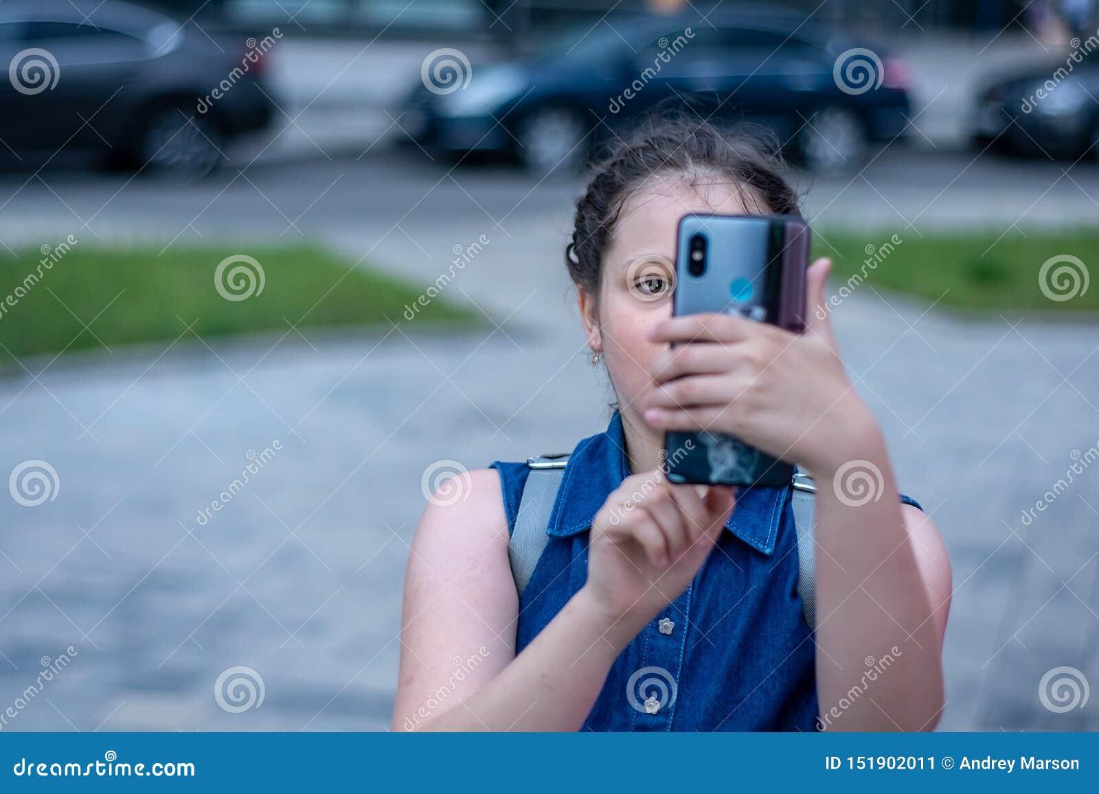 女孩在智能手机做照片 有智能手机的现代生活女孩