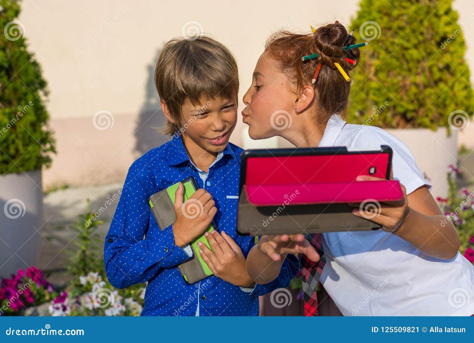 女孩在桌上亲吻她的弟弟并且做selfie