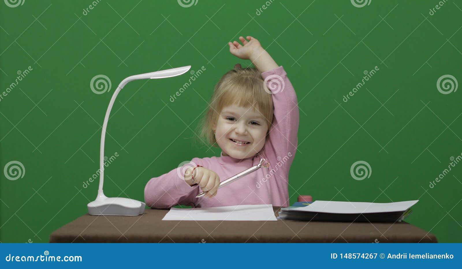 女孩在桌上 因为她认识答复对问题,举她的手