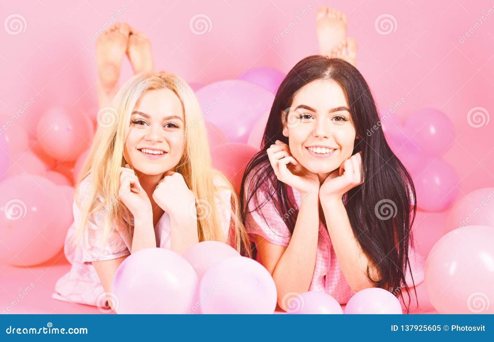 女孩在腹部在气球附近,桃红色背景放置 闲话概念 白肤金发和深色在微笑的面孔获得乐趣在