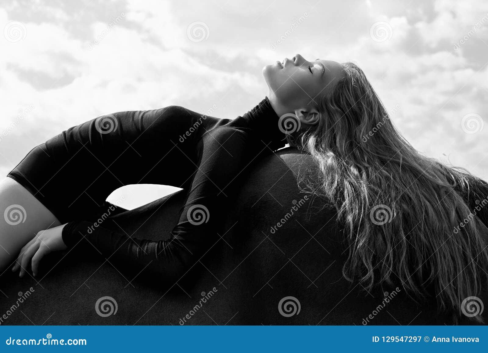 女孩在领域的一匹马弯曲的车手谎言 妇女的时尚画象和母马是马在天空的村庄