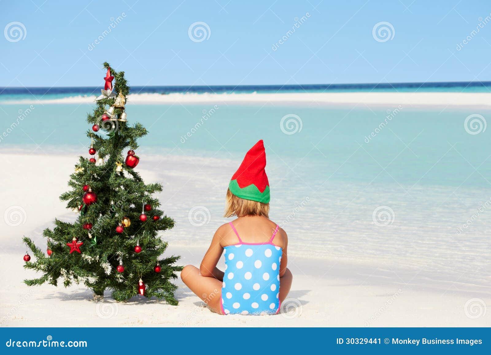 女孩坐与圣诞树和帽子的海滩