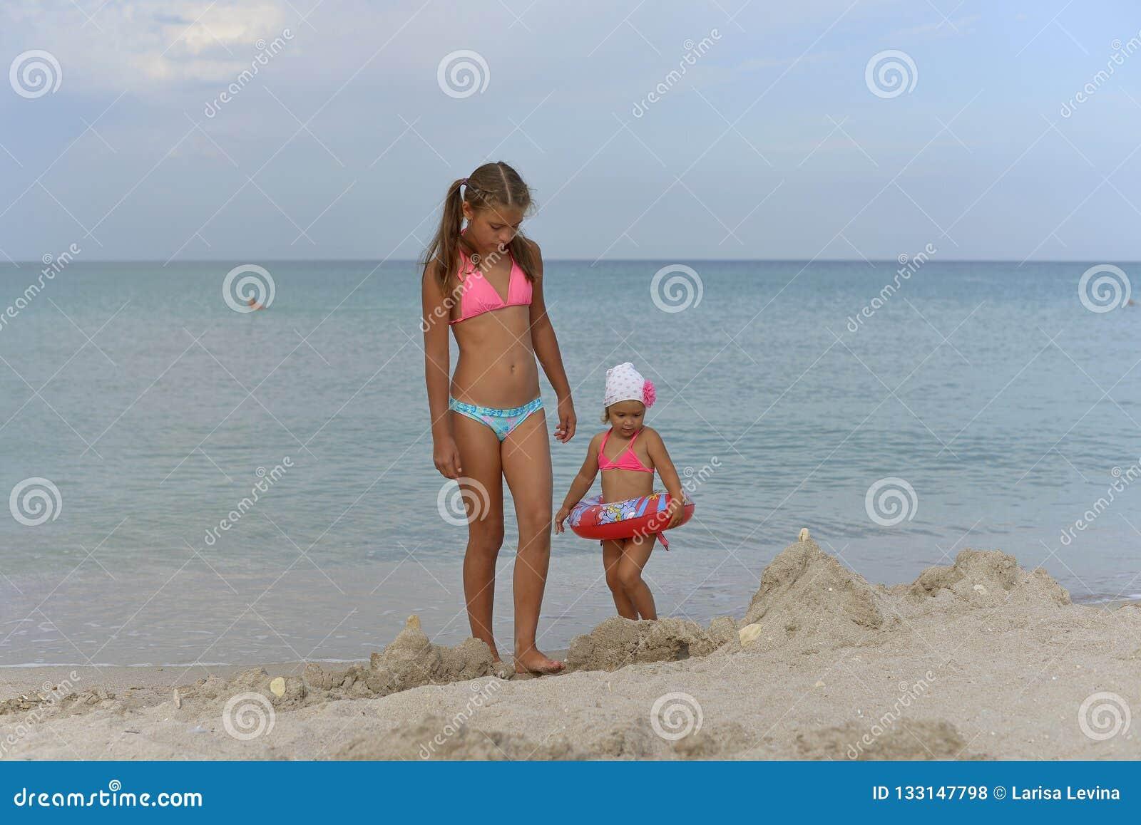 女孩姐妹在沙滩的比基尼泳装站立在一个夏日