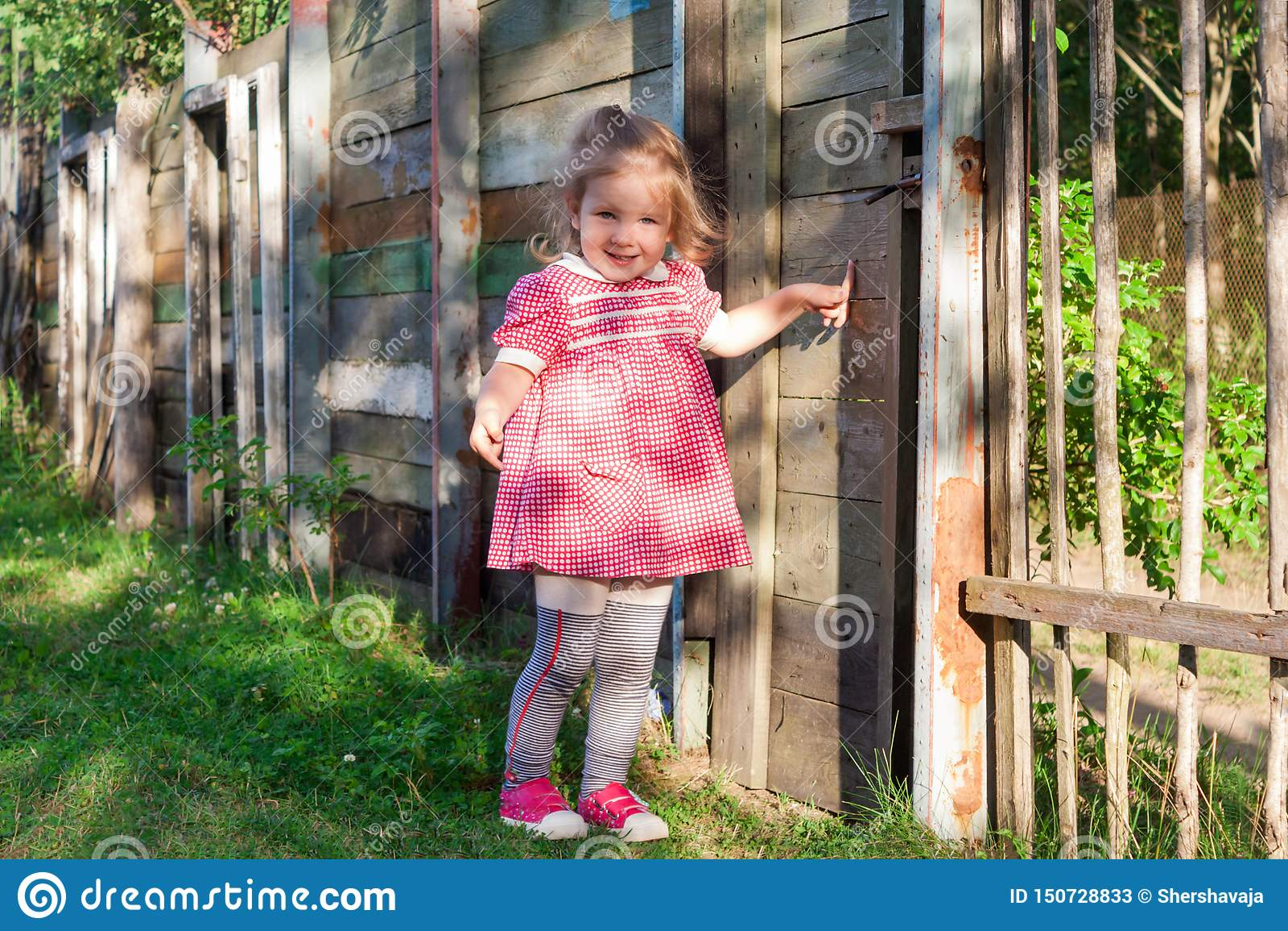 女孩婴孩在篱芭显示在门的一个手指