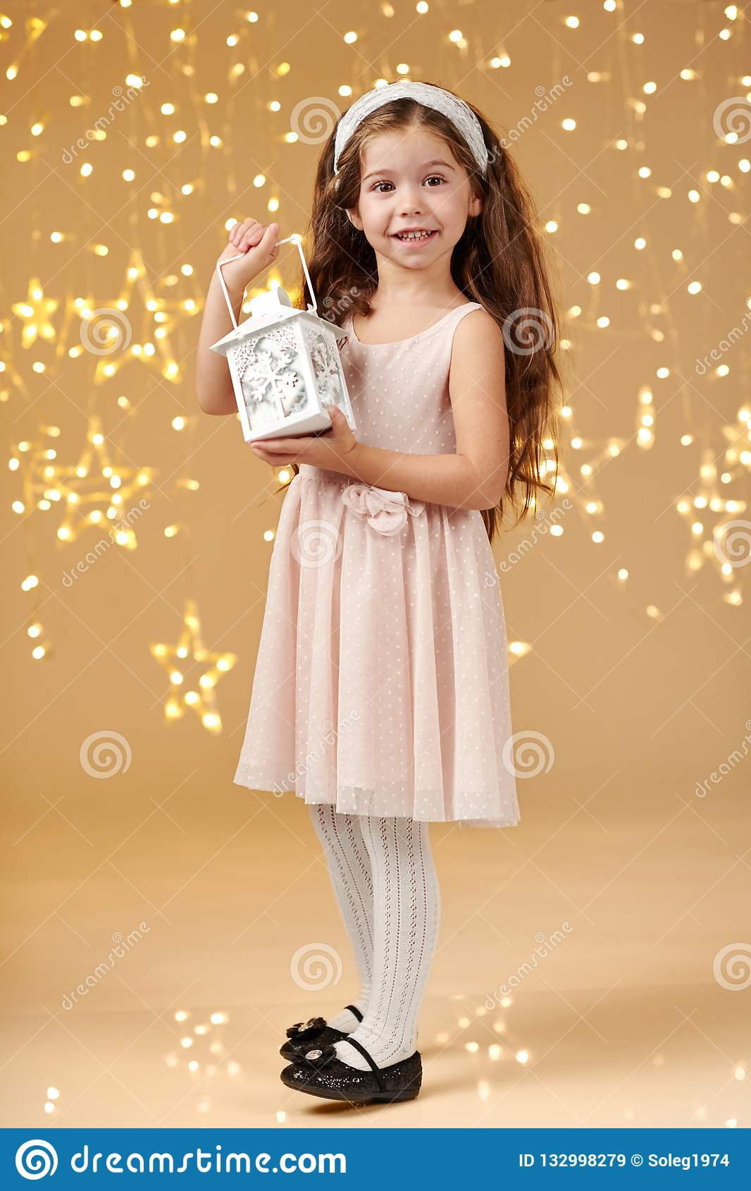 女孩孩子摆在与在圣诞灯的灯笼,黄色背景,桃红色礼服