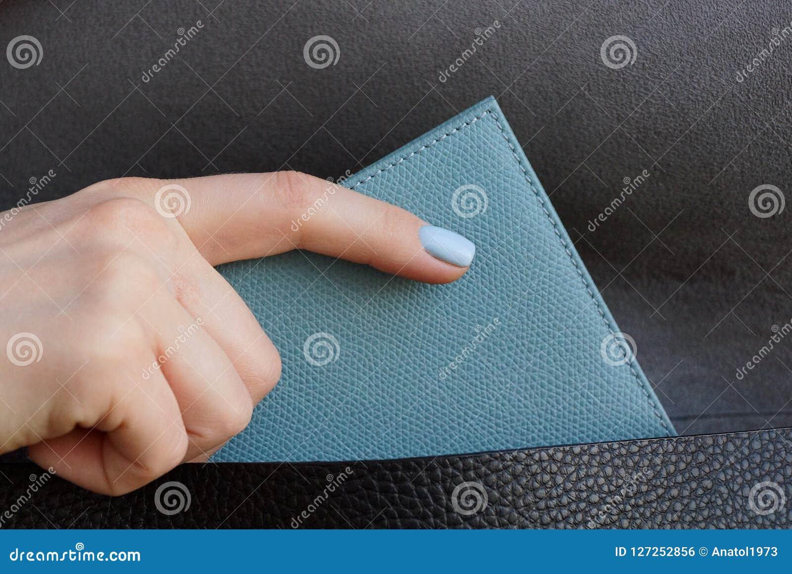 女孩手去掉从一个黑皮包的一个灰色钱包