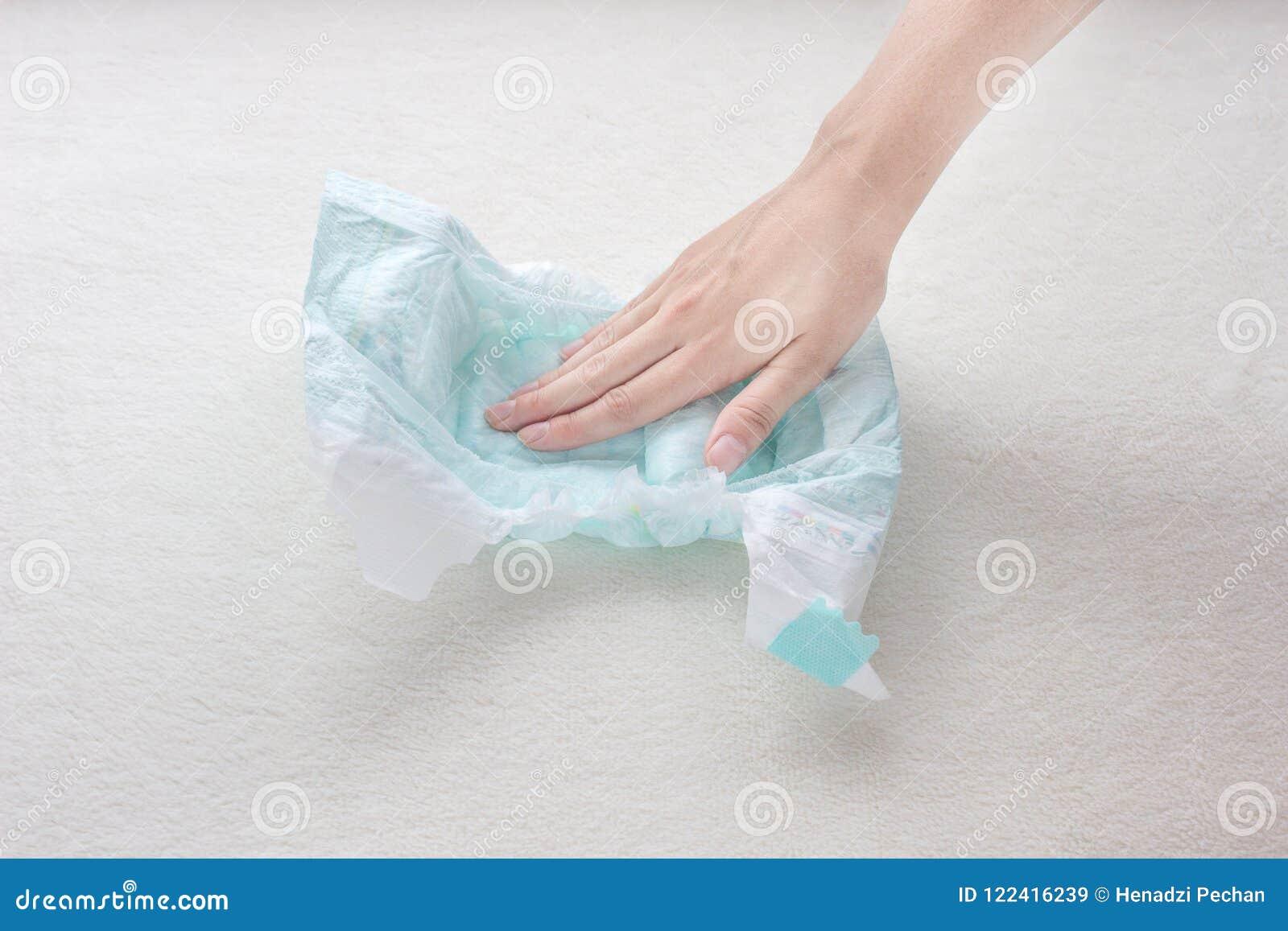女孩手接触婴孩尿布,特写镜头的湿气吸收能力