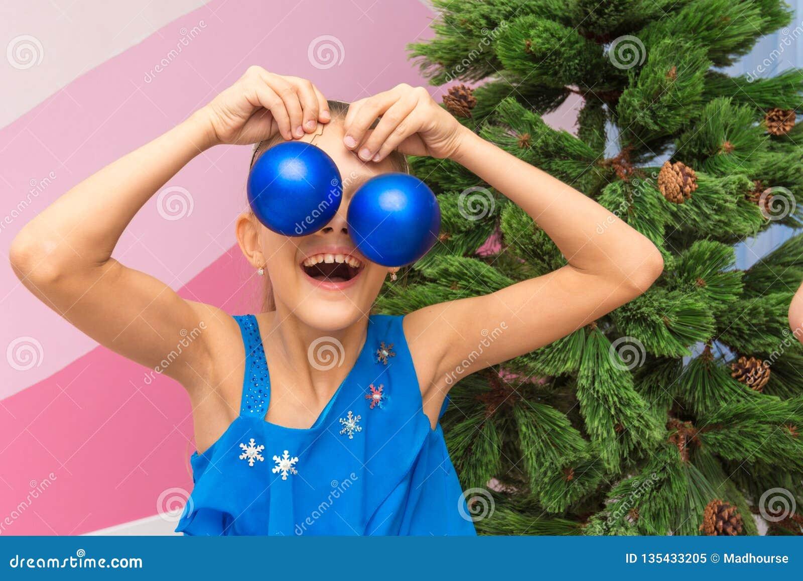 女孩投入了大圣诞节球对她的眼睛
