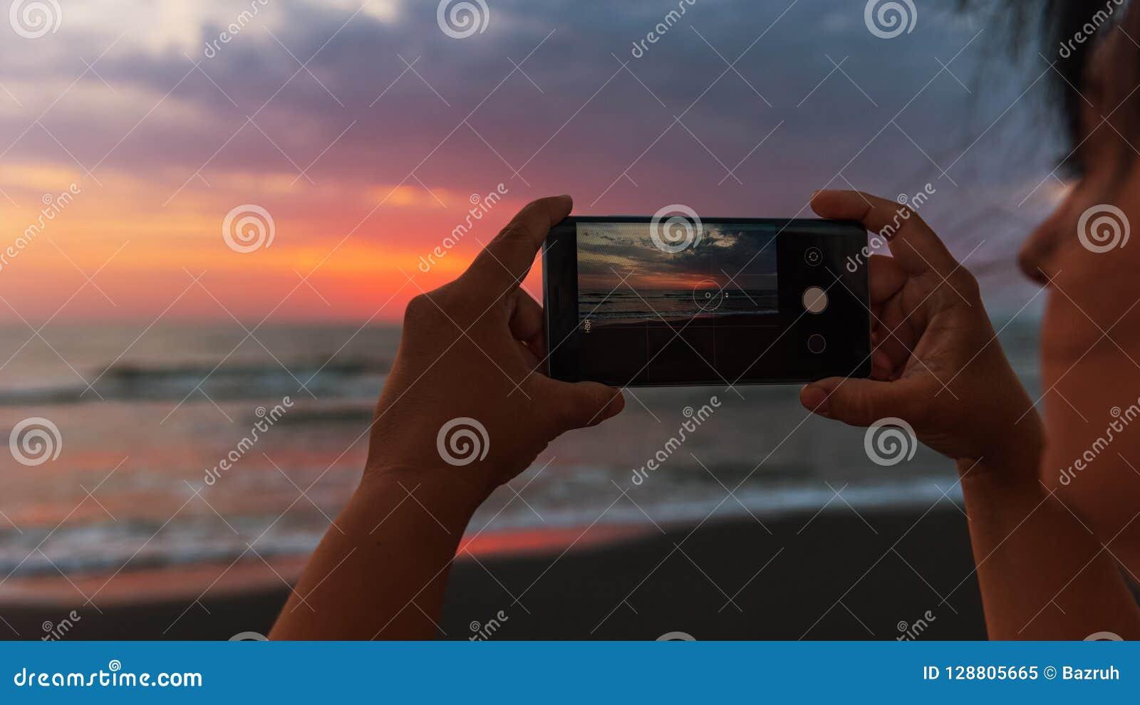女孩拍在智能手机的照片,在海的黎明