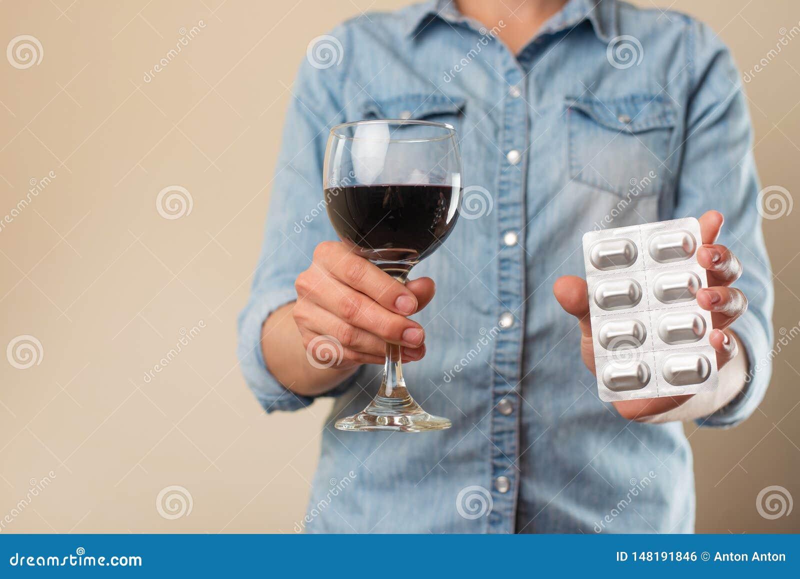 女孩拿着与一杯的一个药片酒,对药物的一个禁令酒精的,治疗选择或酒精