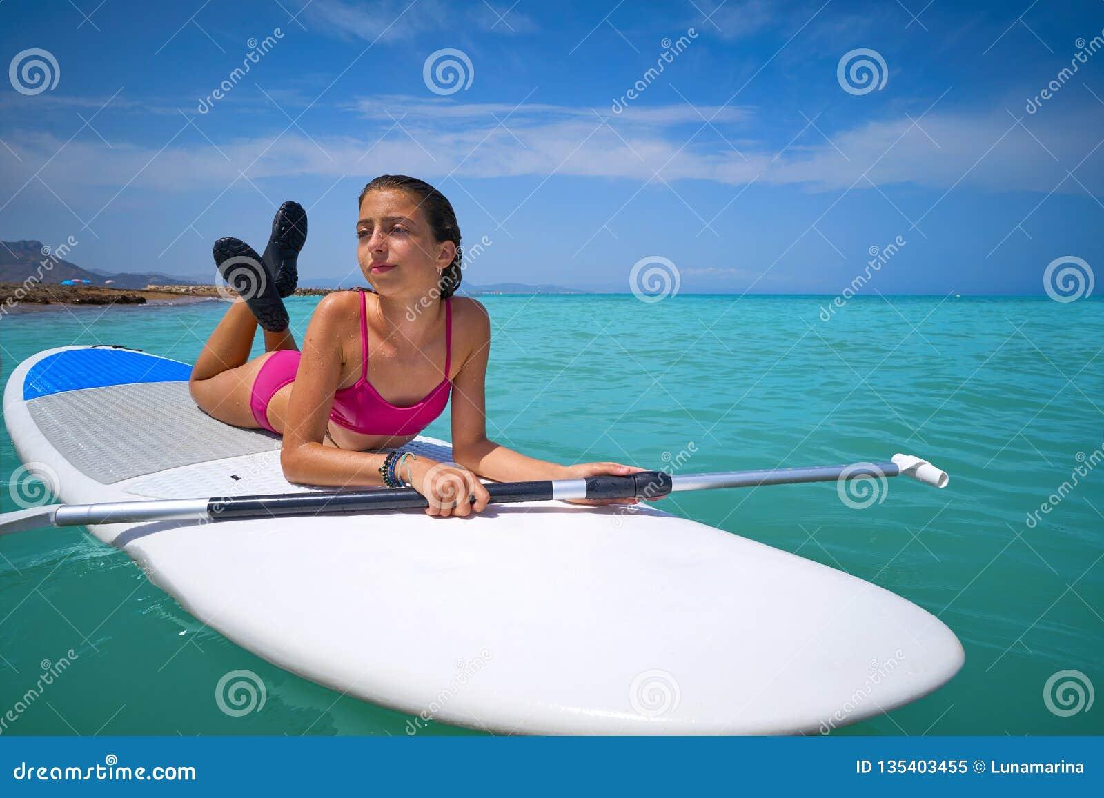 女孩放松了说谎在桨水橇板一口
