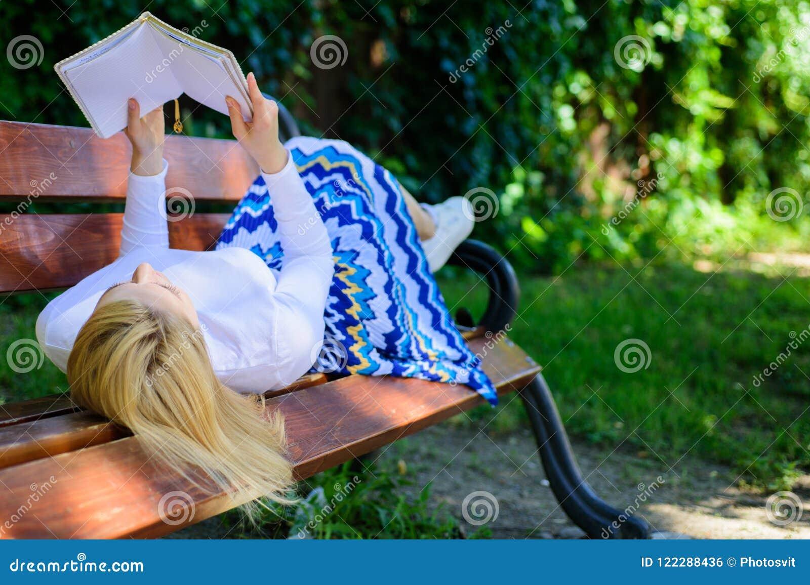 女孩放置放松与书,绿色自然背景的长凳公园 妇女花费与书的休闲 有趣的书 聪明