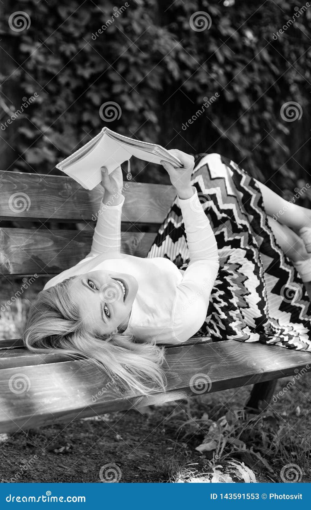 女孩放置放松与书,绿色自然背景的长凳公园 妇女花费与书的休闲 自已的时刻