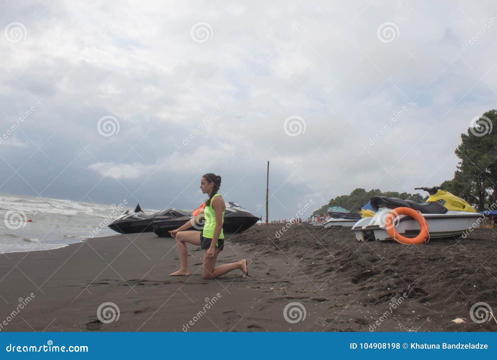 女孩救生员,有救生当班俯视的海的橙色浮体的,海洋海滩 在海滩的水滑行车