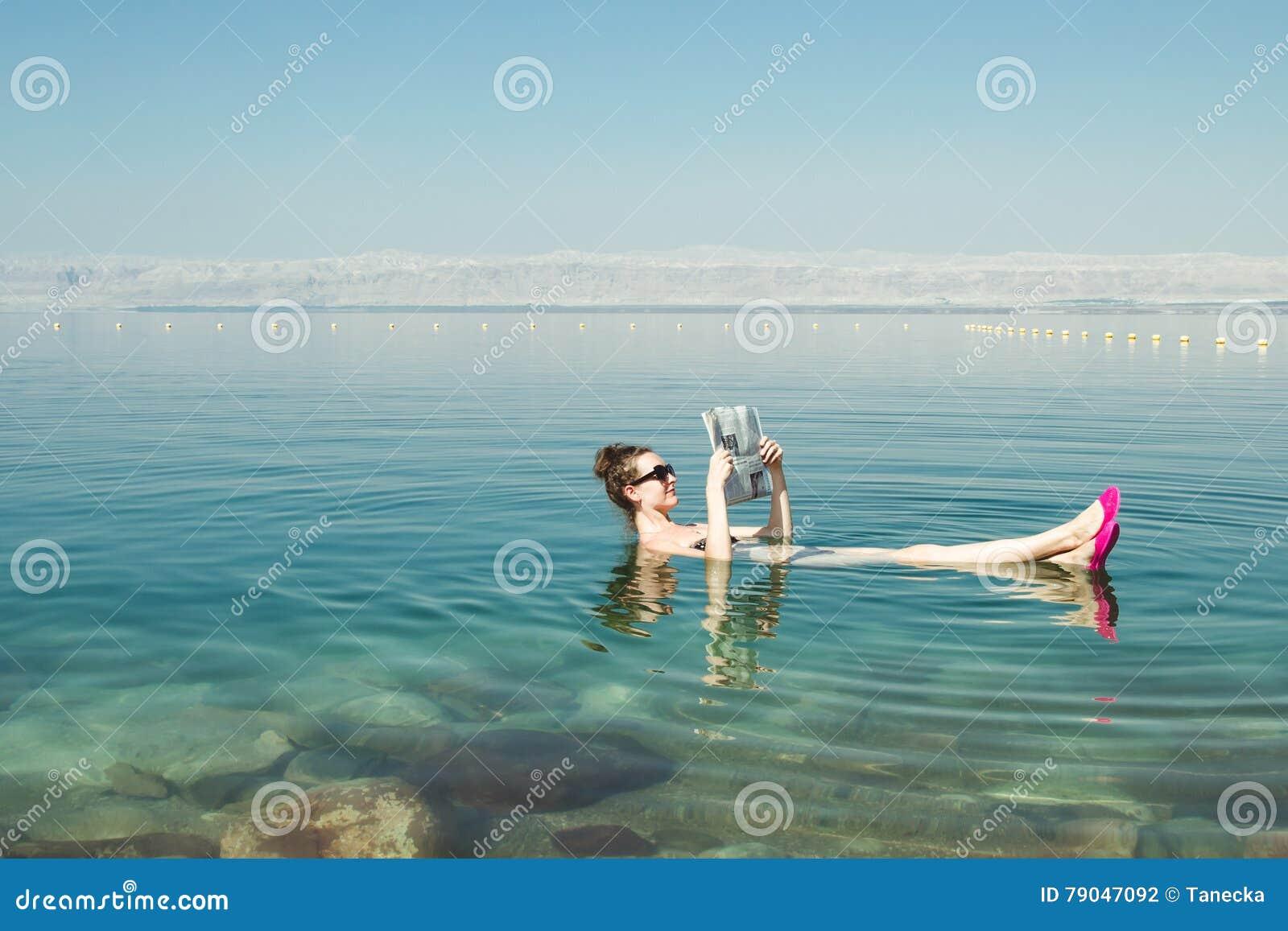 女孩漂浮在表面死海的读书报纸享受夏天太阳和假期 休闲旅游业,健康生活方式,自由的蒂姆