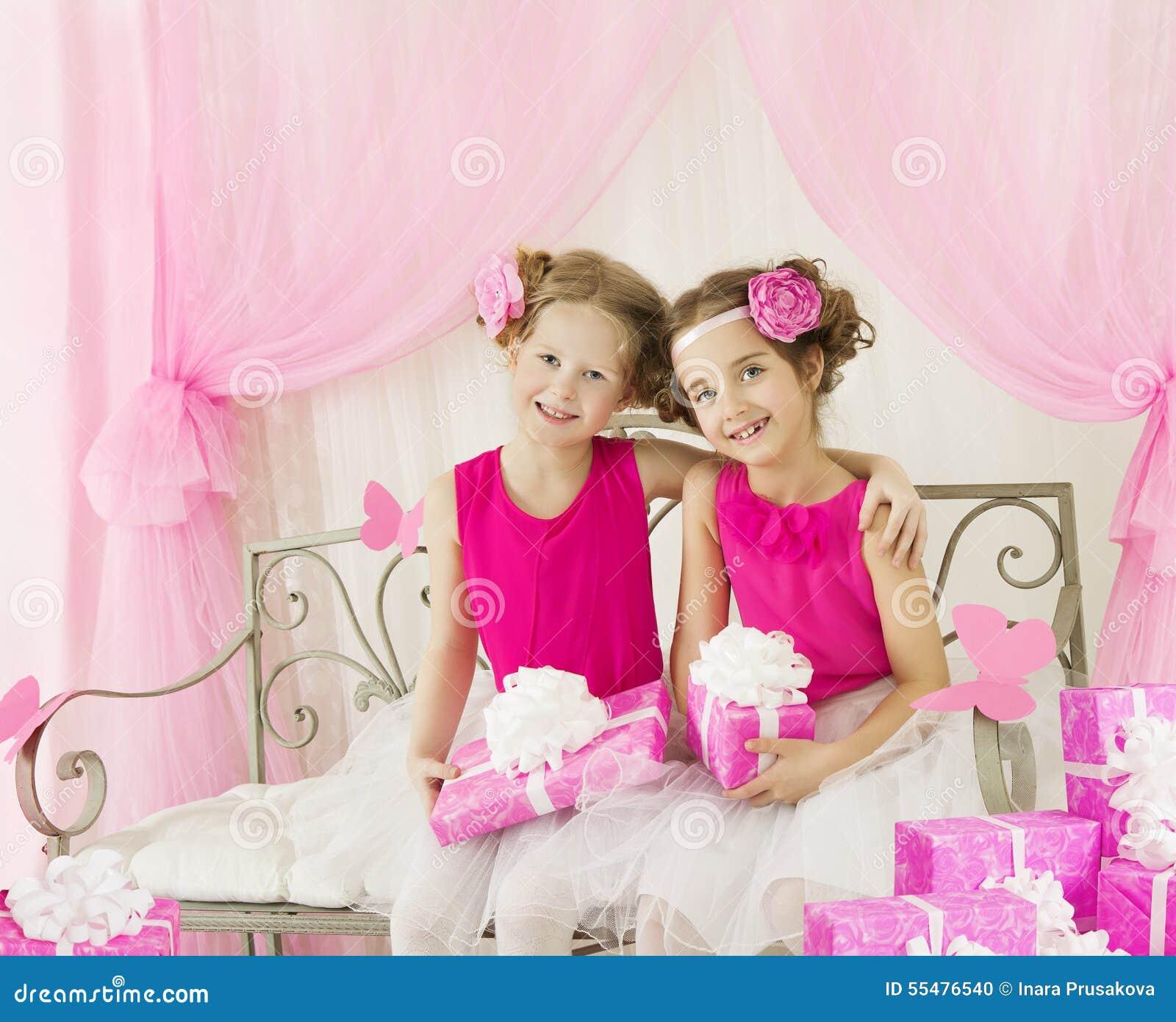 女孩生日,有当前礼物盒的孩子减速火箭的桃红色礼服