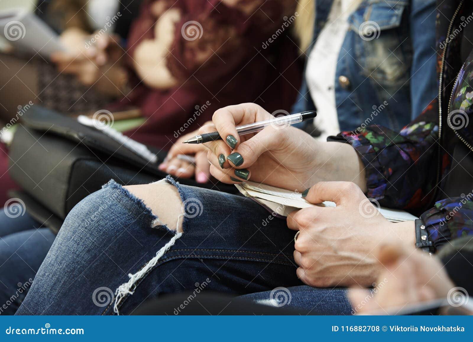 女孩的手有笔和笔记薄的在她的膝盖特写镜头说谎