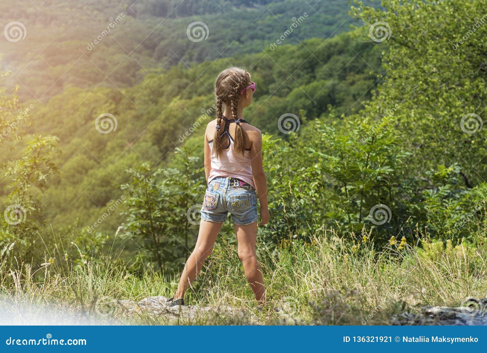 女孩看从上流的山 女孩在一夏天好日子站立小山