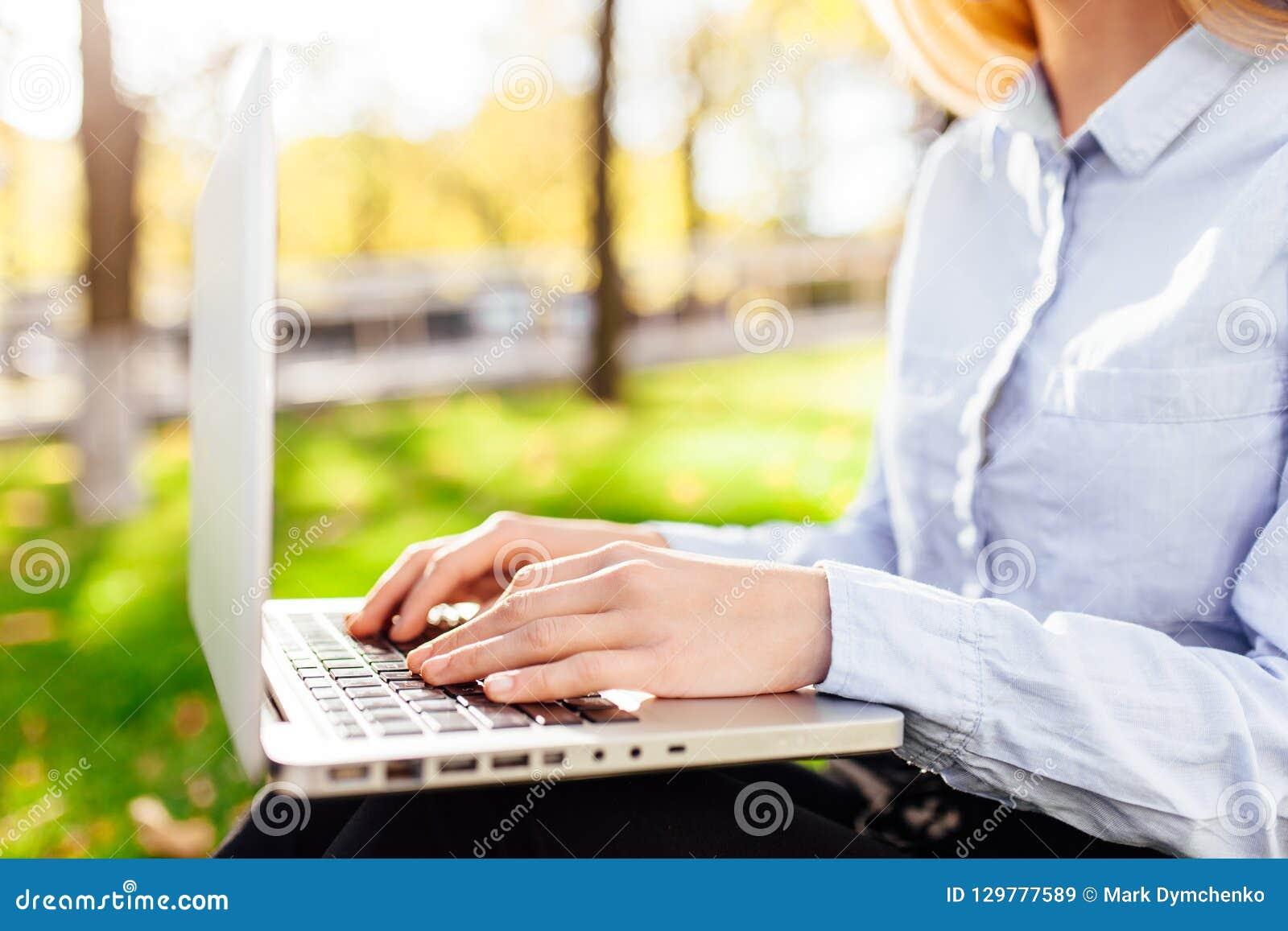 女孩研究膝上型计算机的,手在公园键入文本,特写镜头