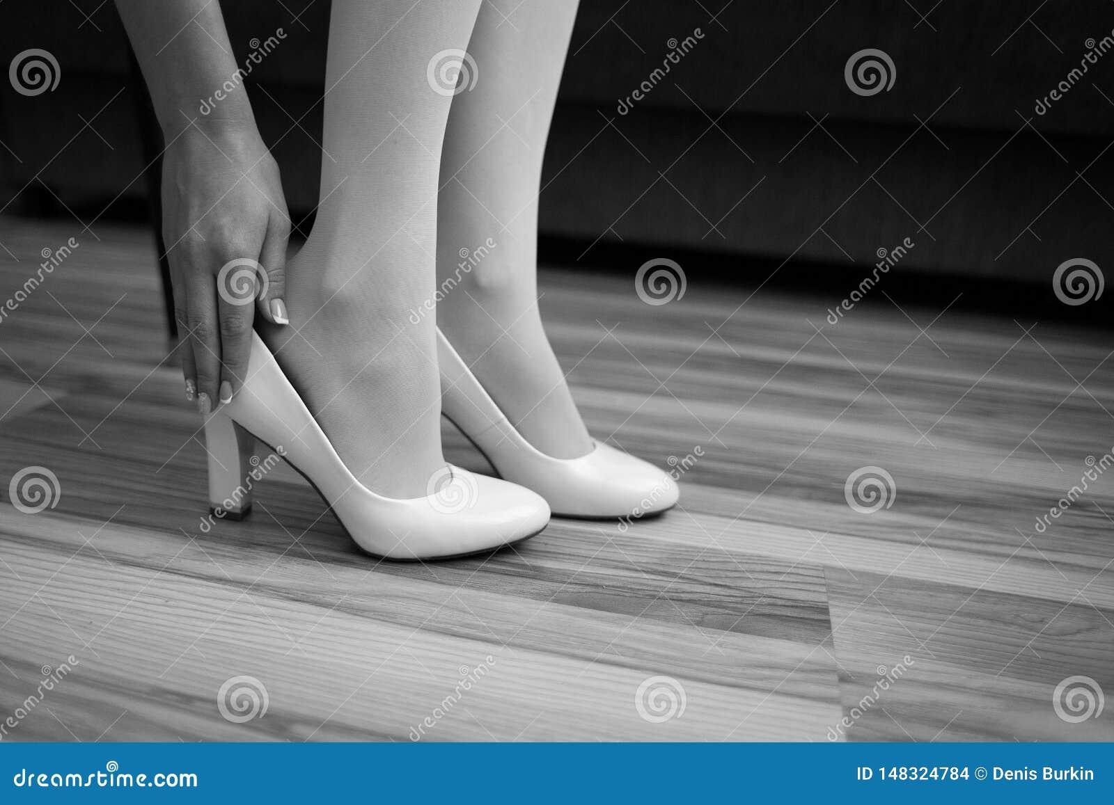 女孩穿在腿的一双鞋子 新娘在内部的早晨投入他的鞋子