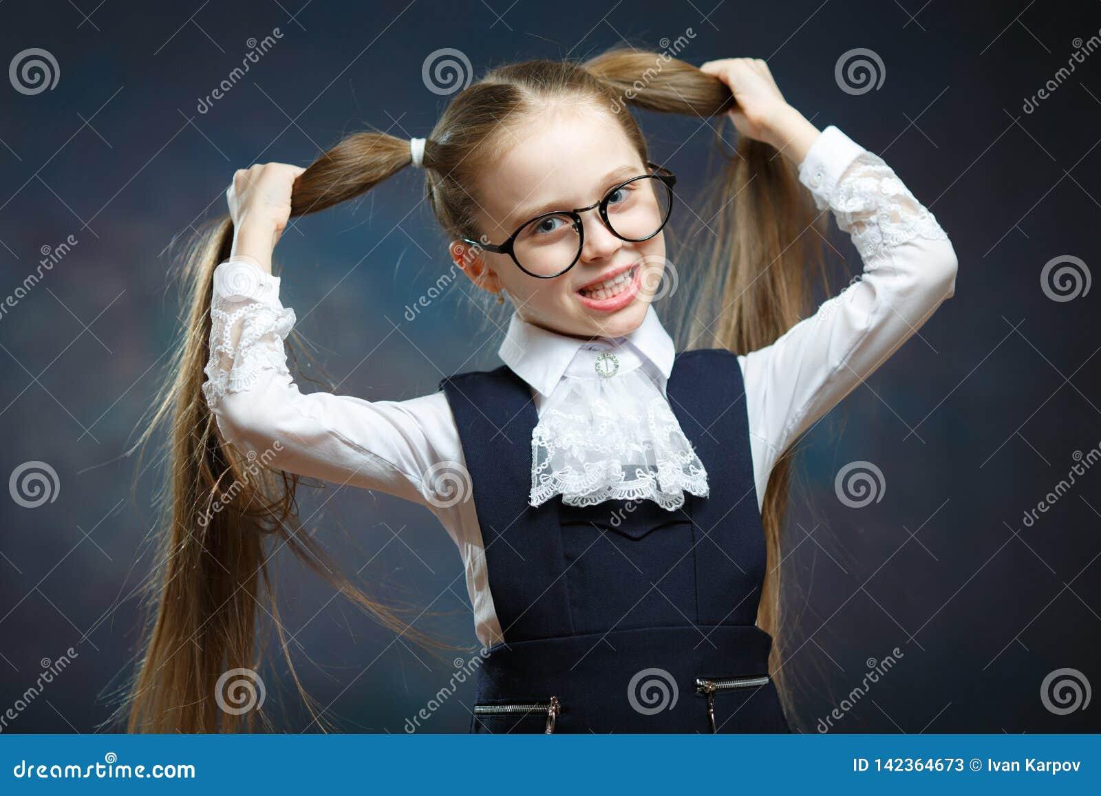 女孩穿戴玻璃看照相机 儿童在马尾辫的举行手