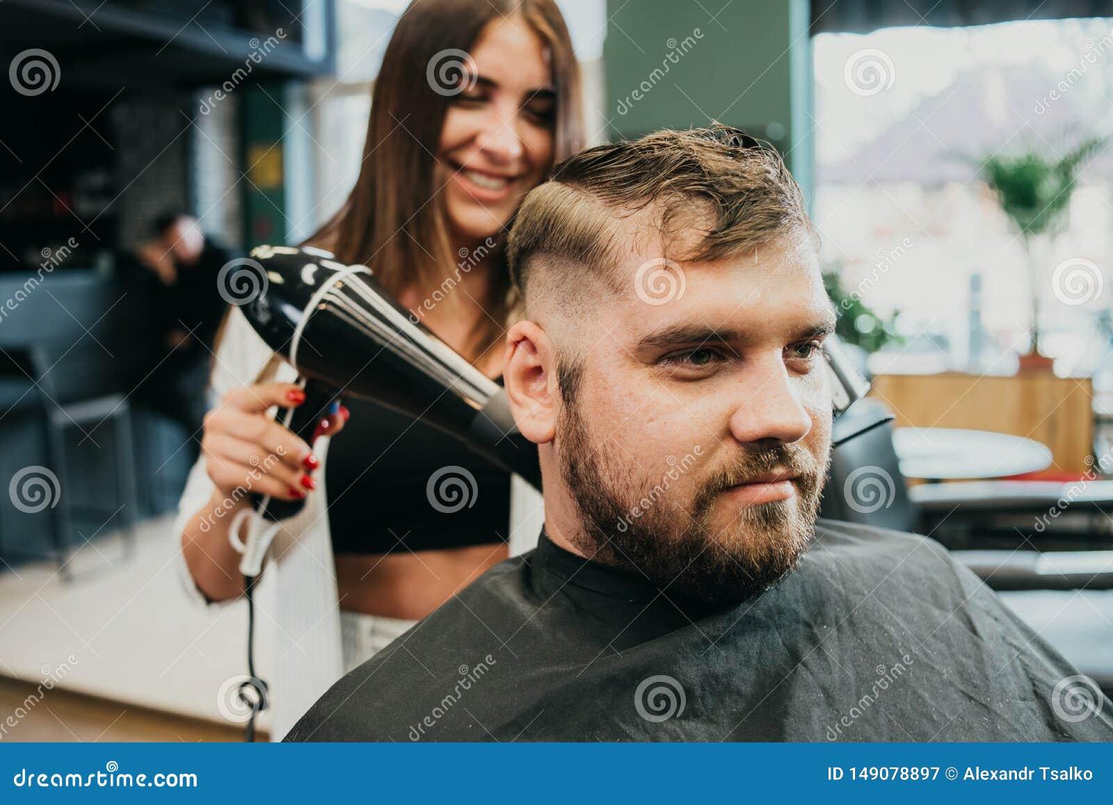 女孩美发师干毛发给沙龙的一个人