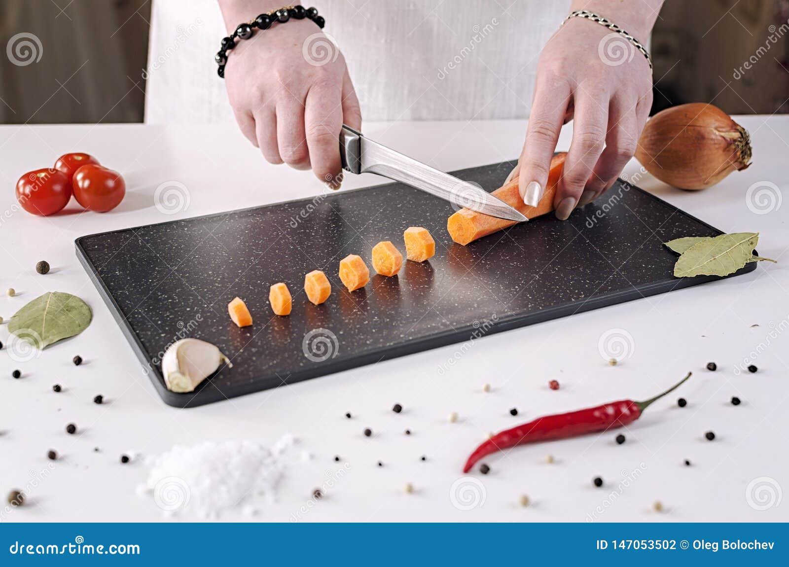 女孩裁减红萝卜到在一个黑切板的小切片里