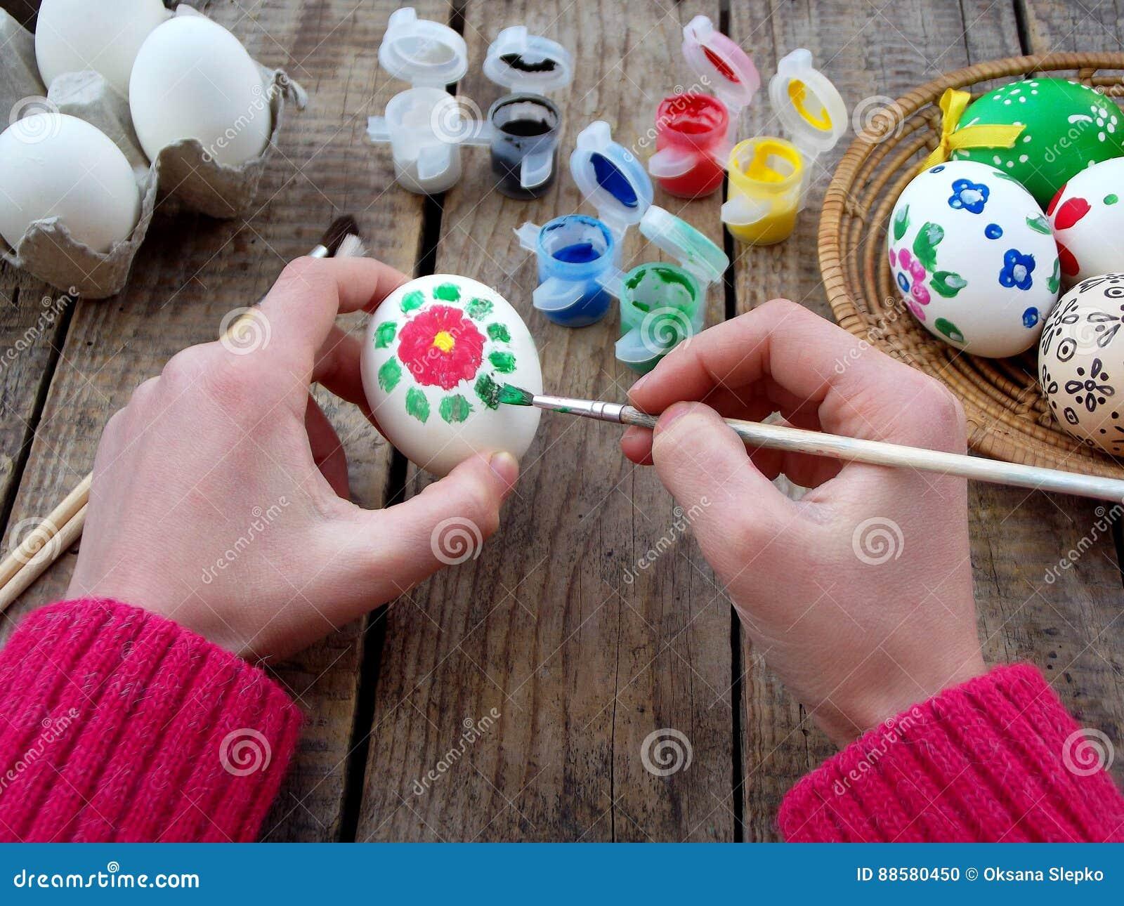女孩递与花卉样式树胶水彩画颜料的绘画鸡蛋 装饰鸡蛋 背景面包软绵绵地结块复活节彩蛋酥皮点心准备影子白色