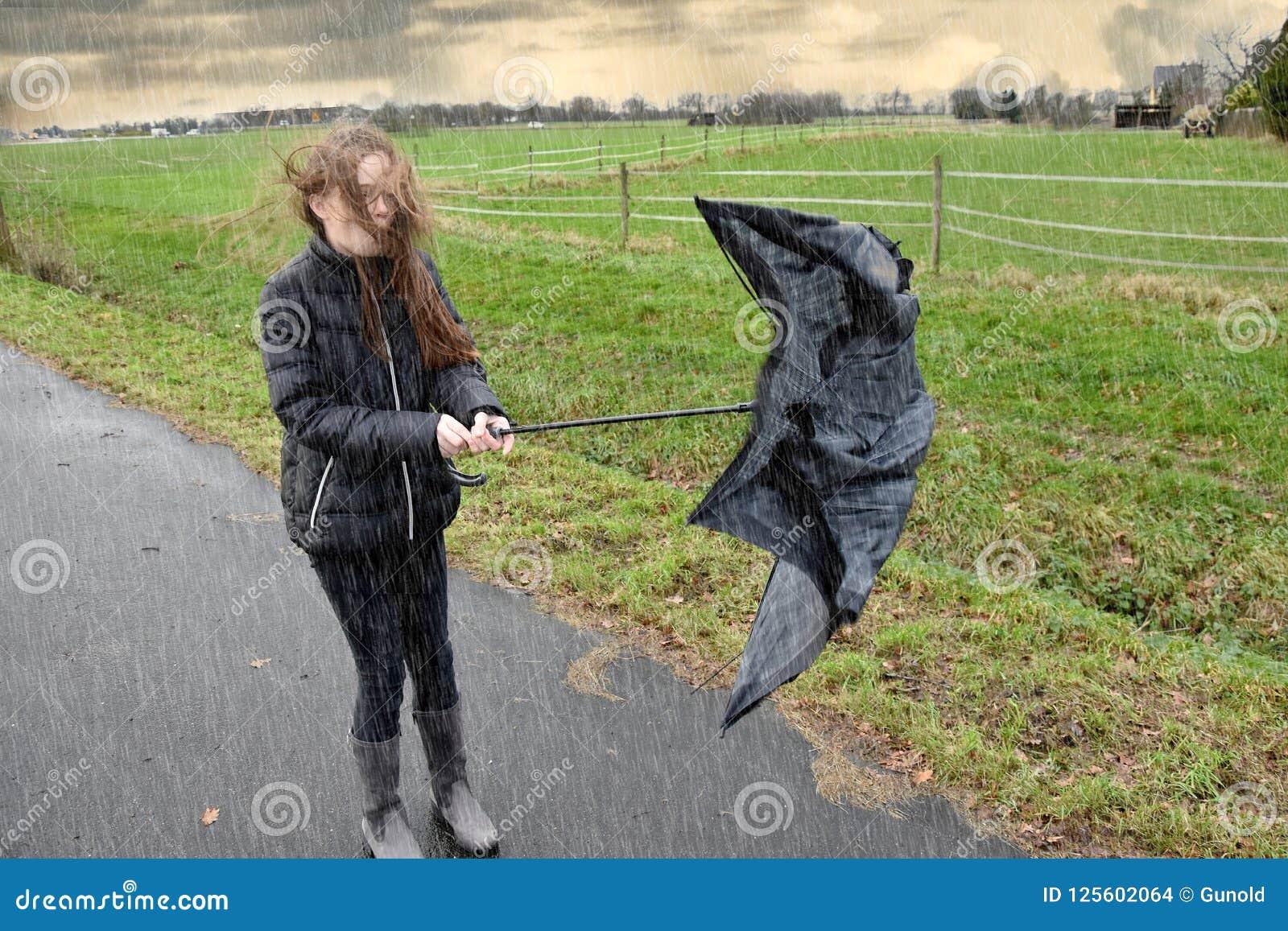 女孩通过雨走,并且风暴,她的伞是残破的
