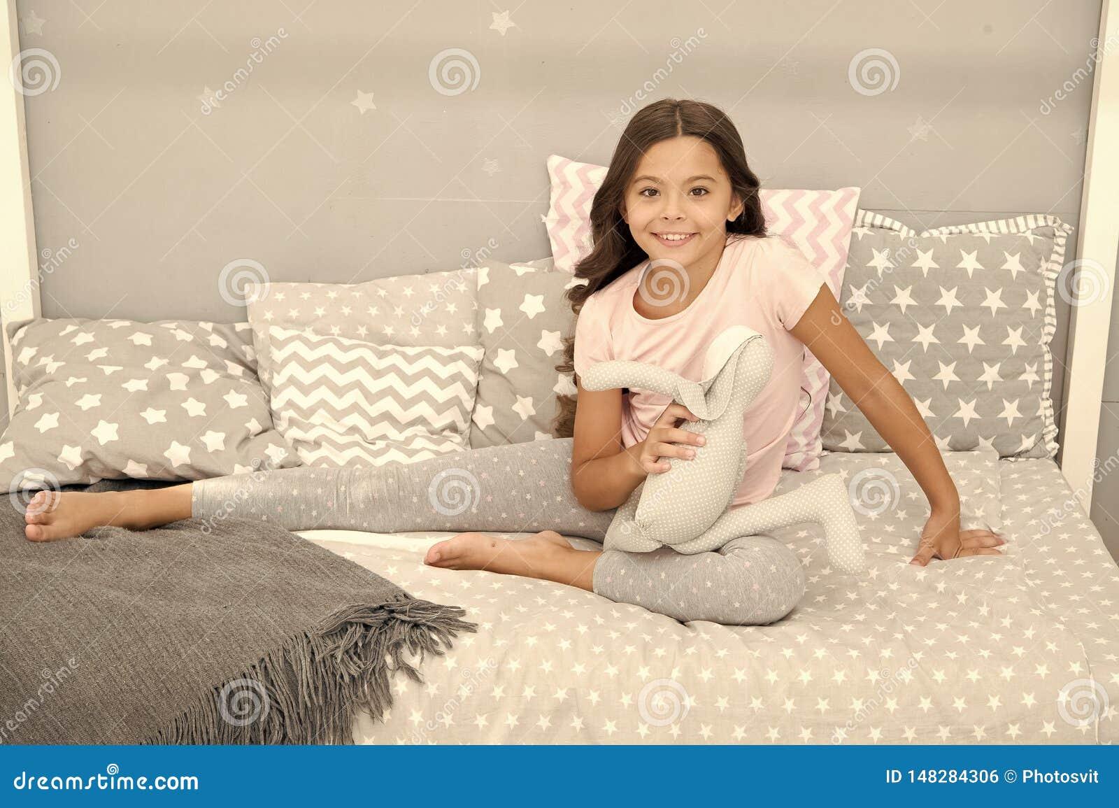 女孩长的卷发喜欢平衡与喜爱的玩具的时间 孩子坐床和戏剧兔宝宝玩具现代卧室内部