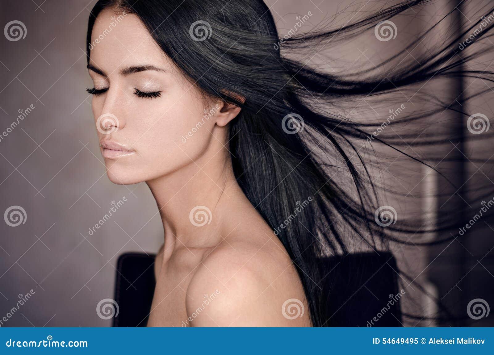 女孩题材的剧烈的画象:一个美丽的孤独的女孩的画象有飞行头发的在黑暗的背景隔绝的风