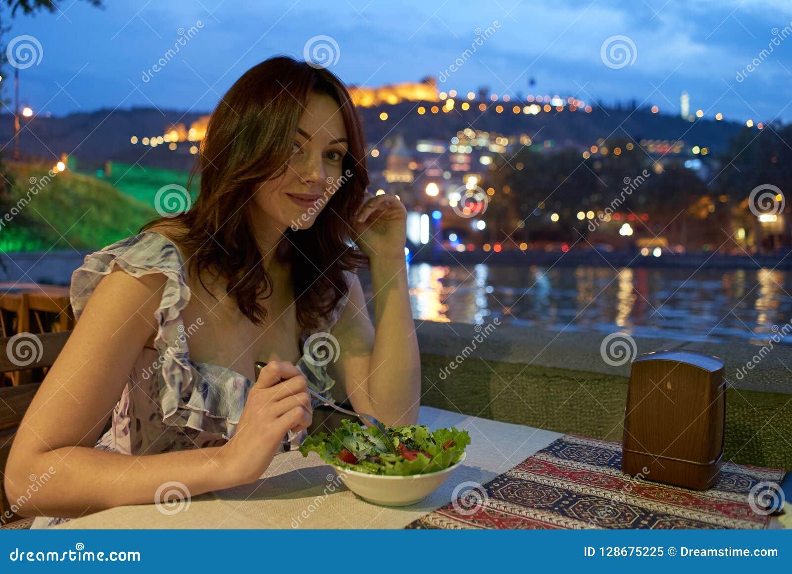 女孩,夜,在一个室外咖啡馆的晚餐