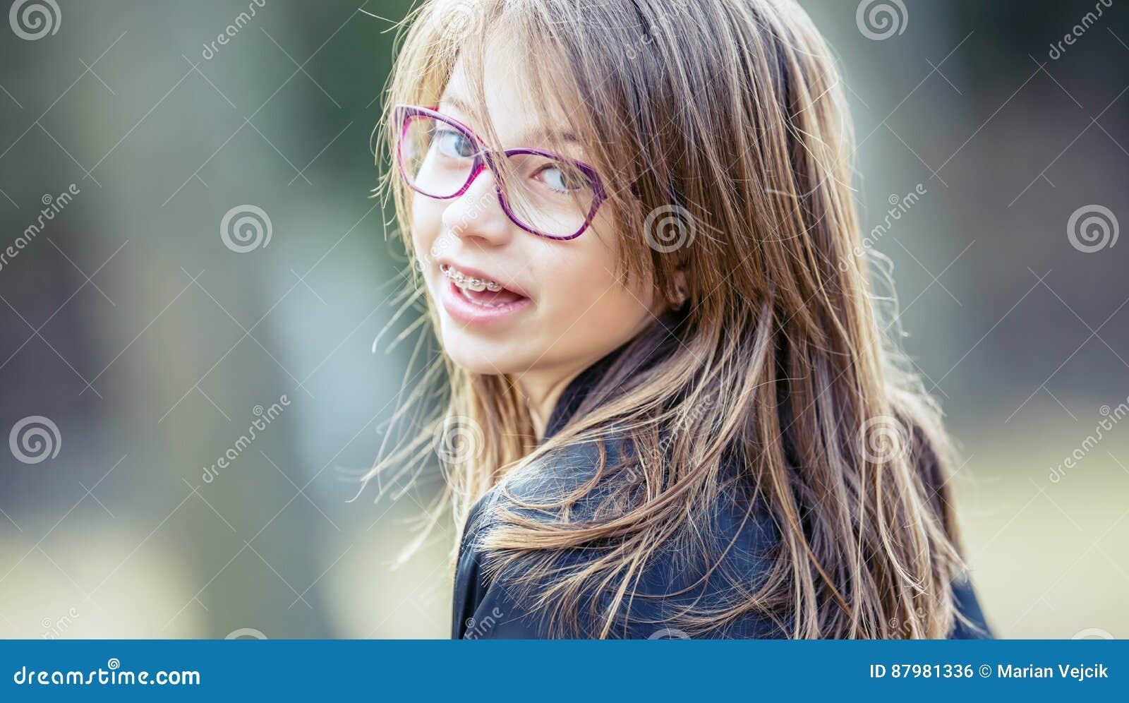 女孩 青少年 前青少年 戴眼镜的女孩 有牙括号的女孩 年轻逗人喜爱的白种人白肤金发的女孩佩带的牙括号和玻璃