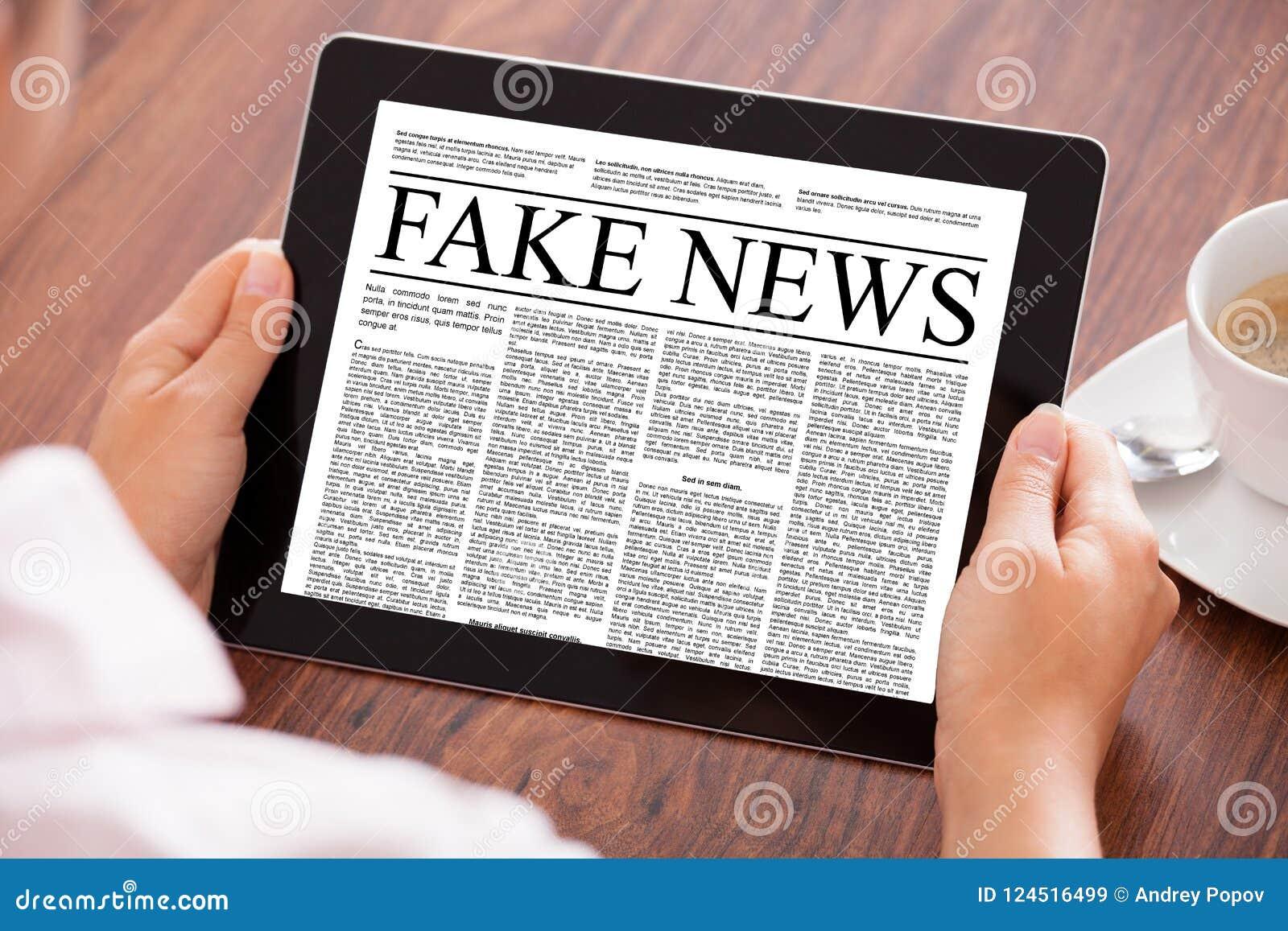 女实业家读书在数字式片剂的伪造品新闻在表上