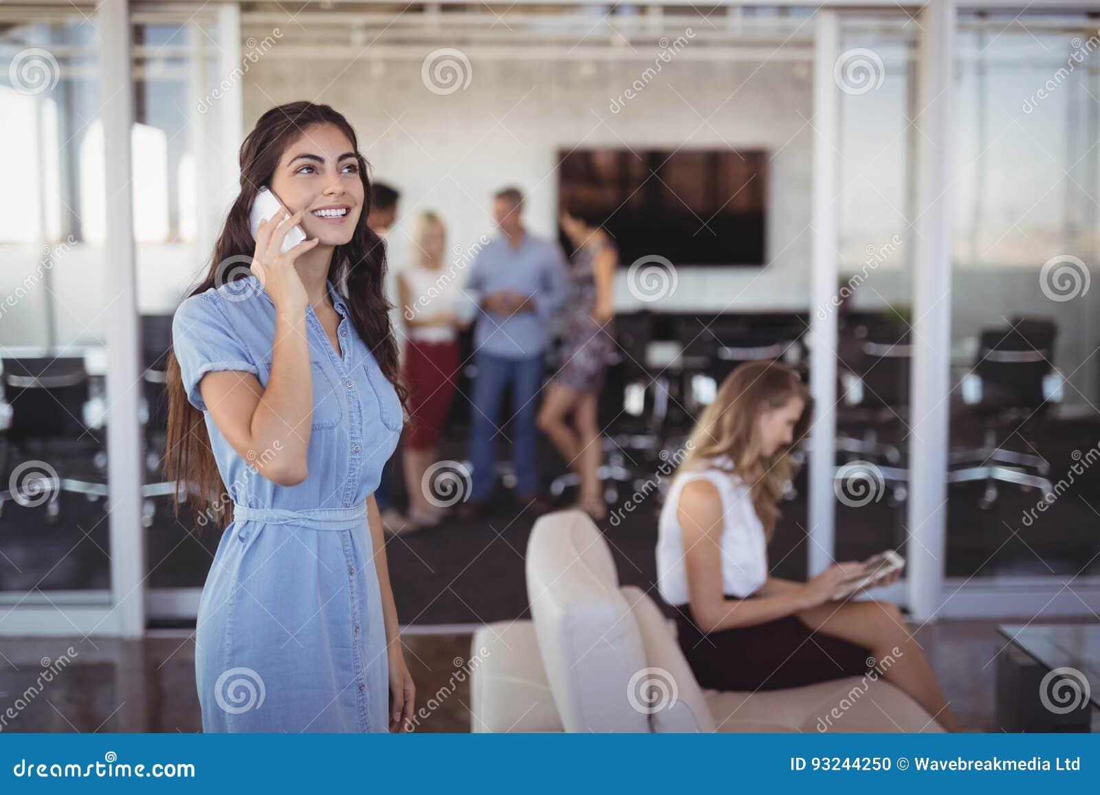 年轻女实业家谈话在手机在创造性的办公室