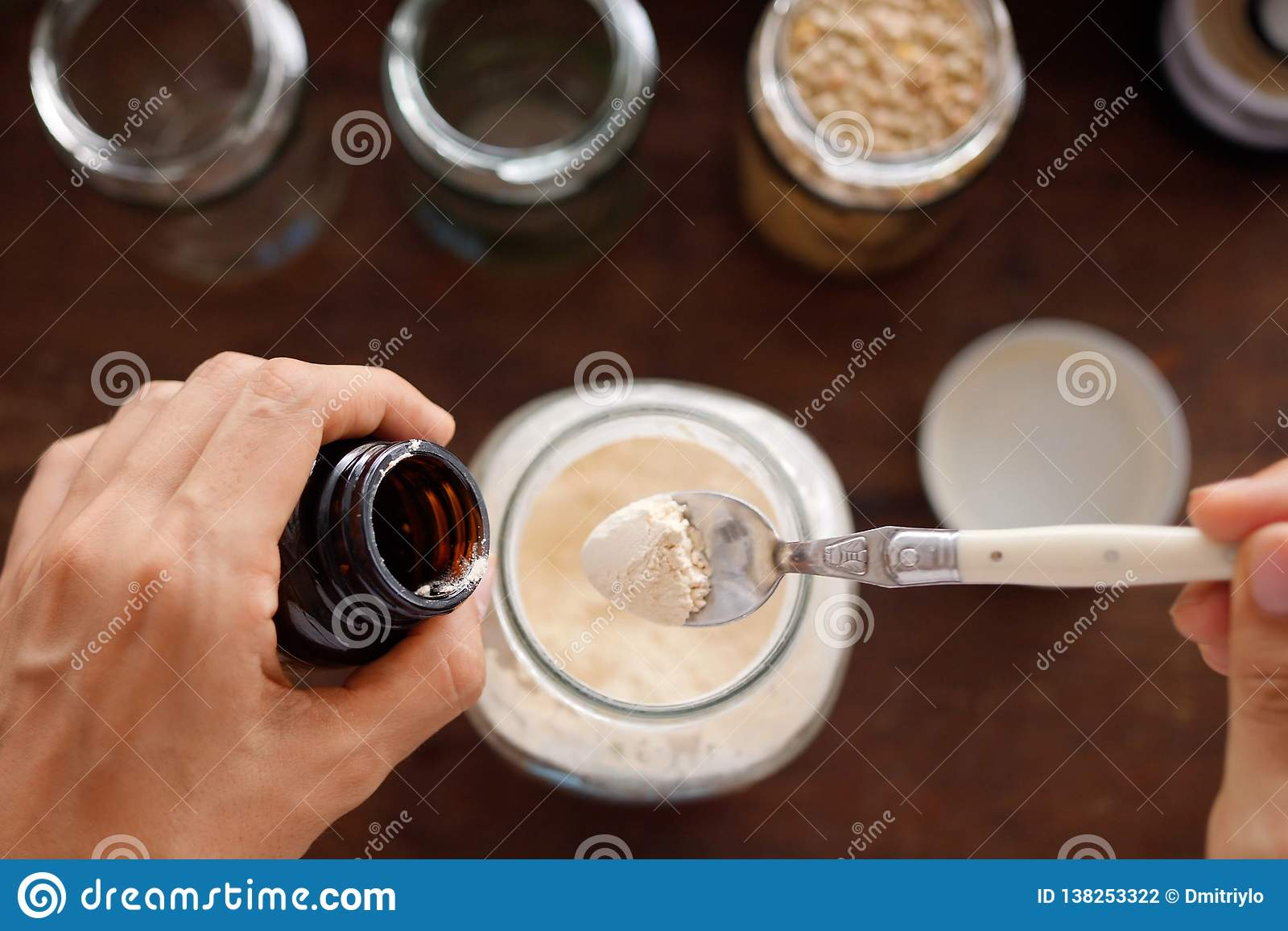 女性倾吐在小玻璃瓶子的大蒜粉末 购物在零的废商店 没有塑料神志清楚的简单派生活方式 减少
