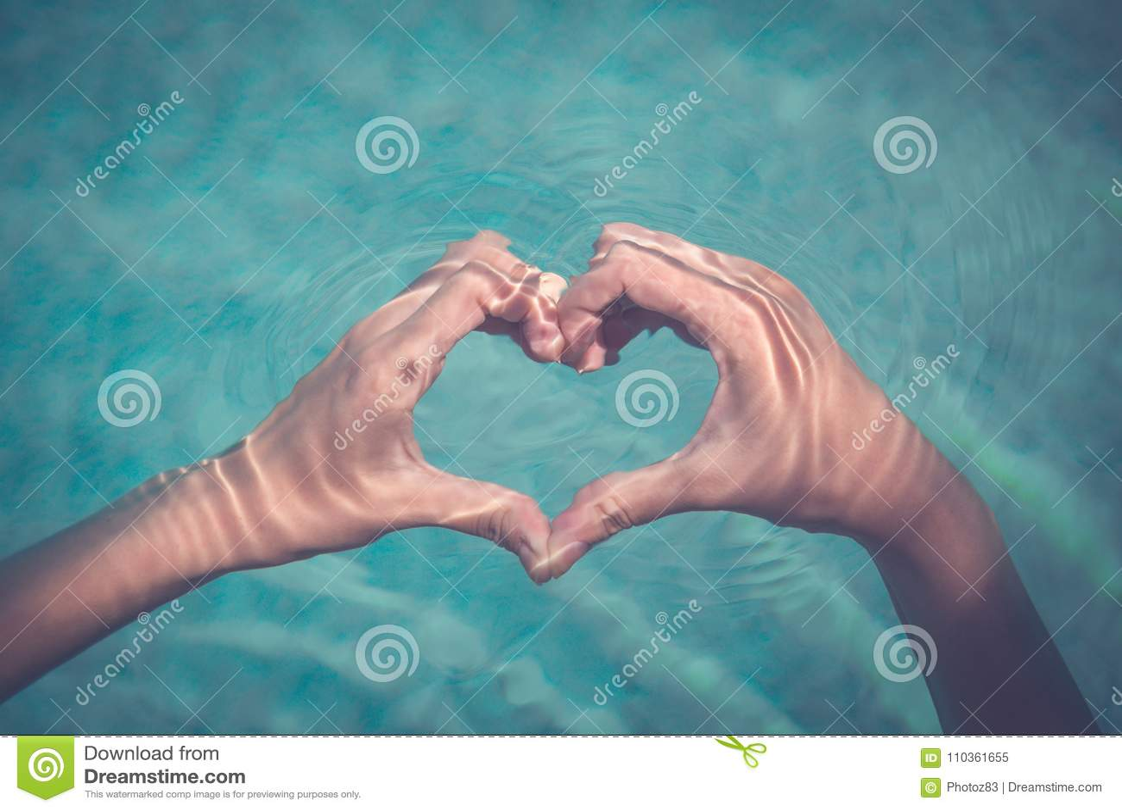 女性制造的心脏形状用手在水中
