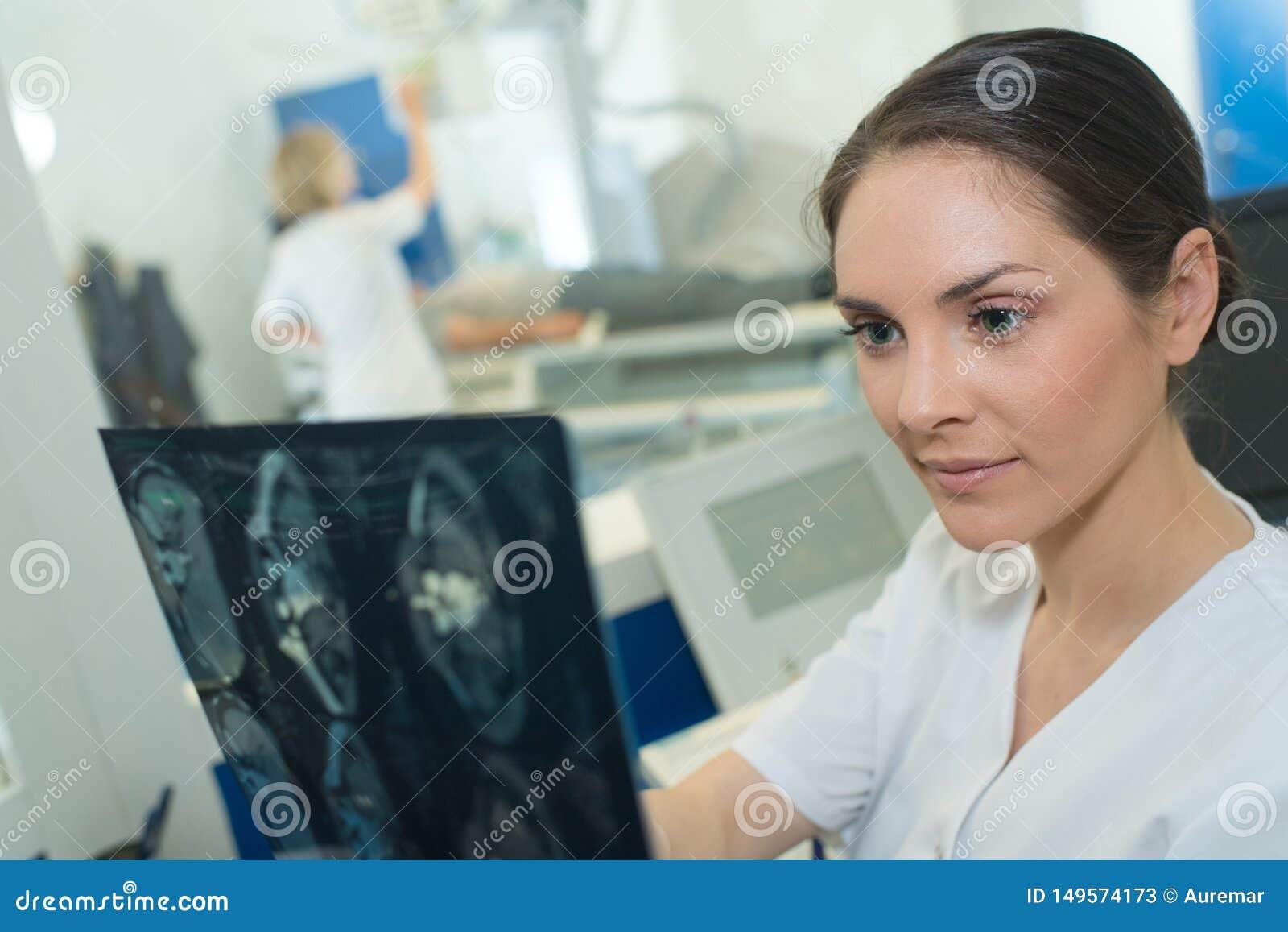 女性医生审查的X-射线报告在医疗办公室