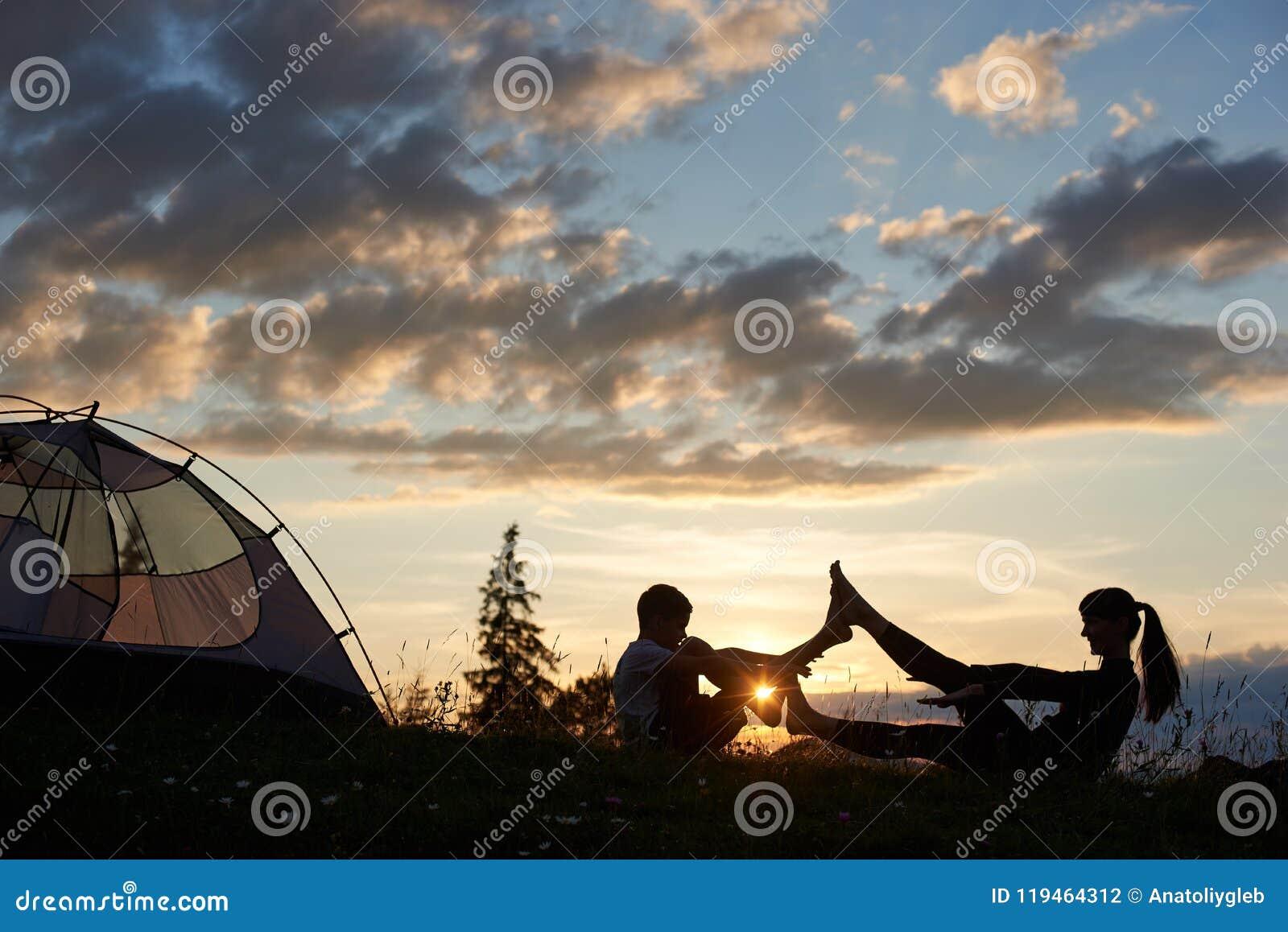 女性和男孩剪影坐在瑜伽姿势的草在破晓在帐篷附近