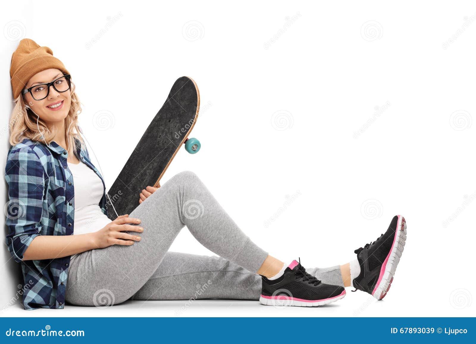 女性在耳机的溜冰者听的音乐