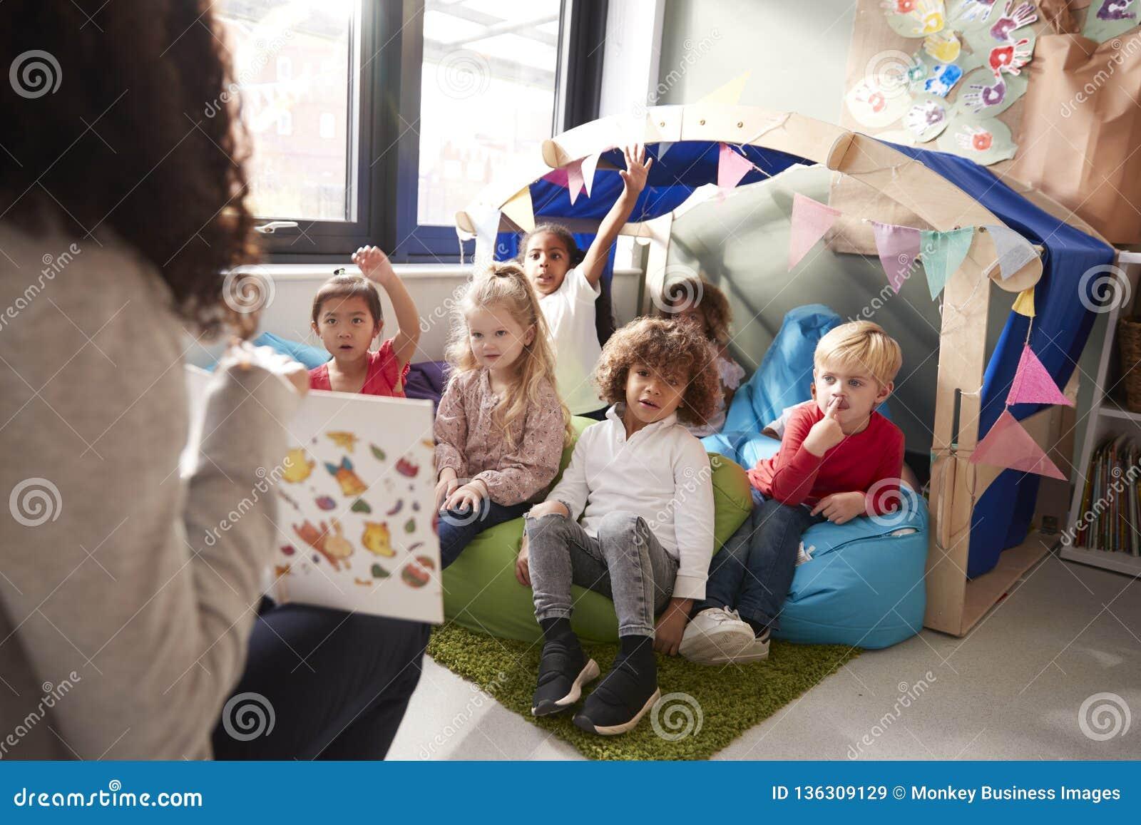 女性婴儿学校老师坐显示书的椅子对一个小组孩子坐辎重袋在一个舒适的角落
